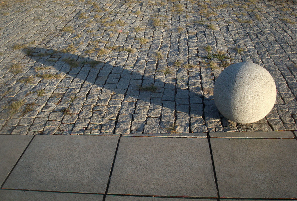 stone ball with a long shadow from a low sun Day High Angle View No People Outdoors Paving Stone Roadway Shadows Slanting Shadows The City Light