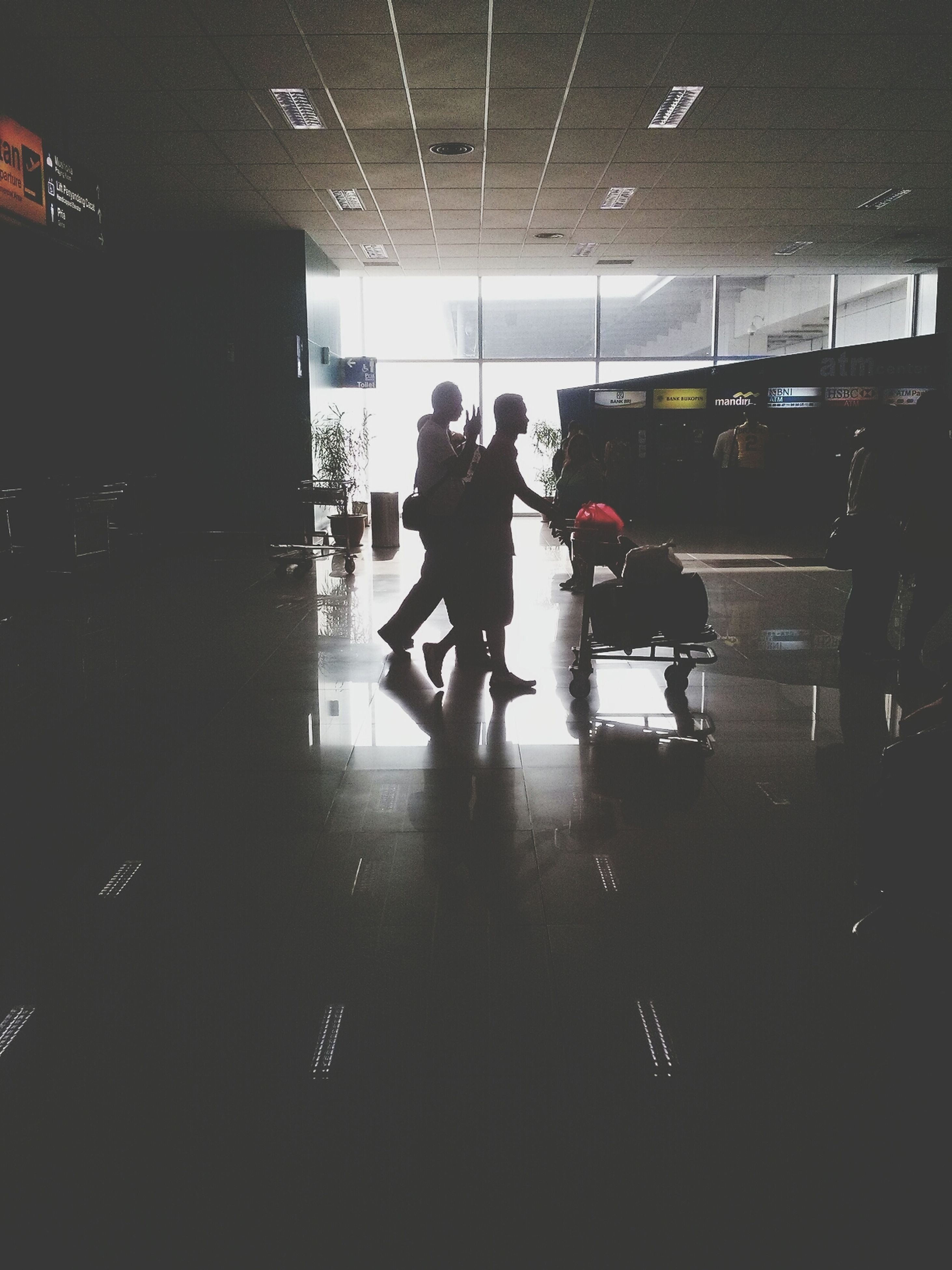 indoors, men, lifestyles, transportation, illuminated, person, passenger, leisure activity, walking, public transportation, mode of transport, travel, full length, medium group of people, subway, airport, subway station, journey, city life