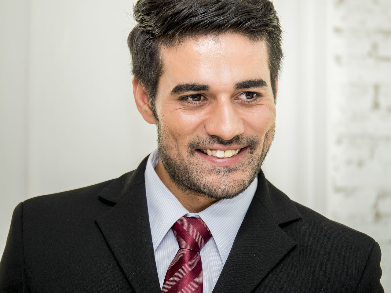 Close-Up Of Smiling Businessman Looking Away While Standing In Office