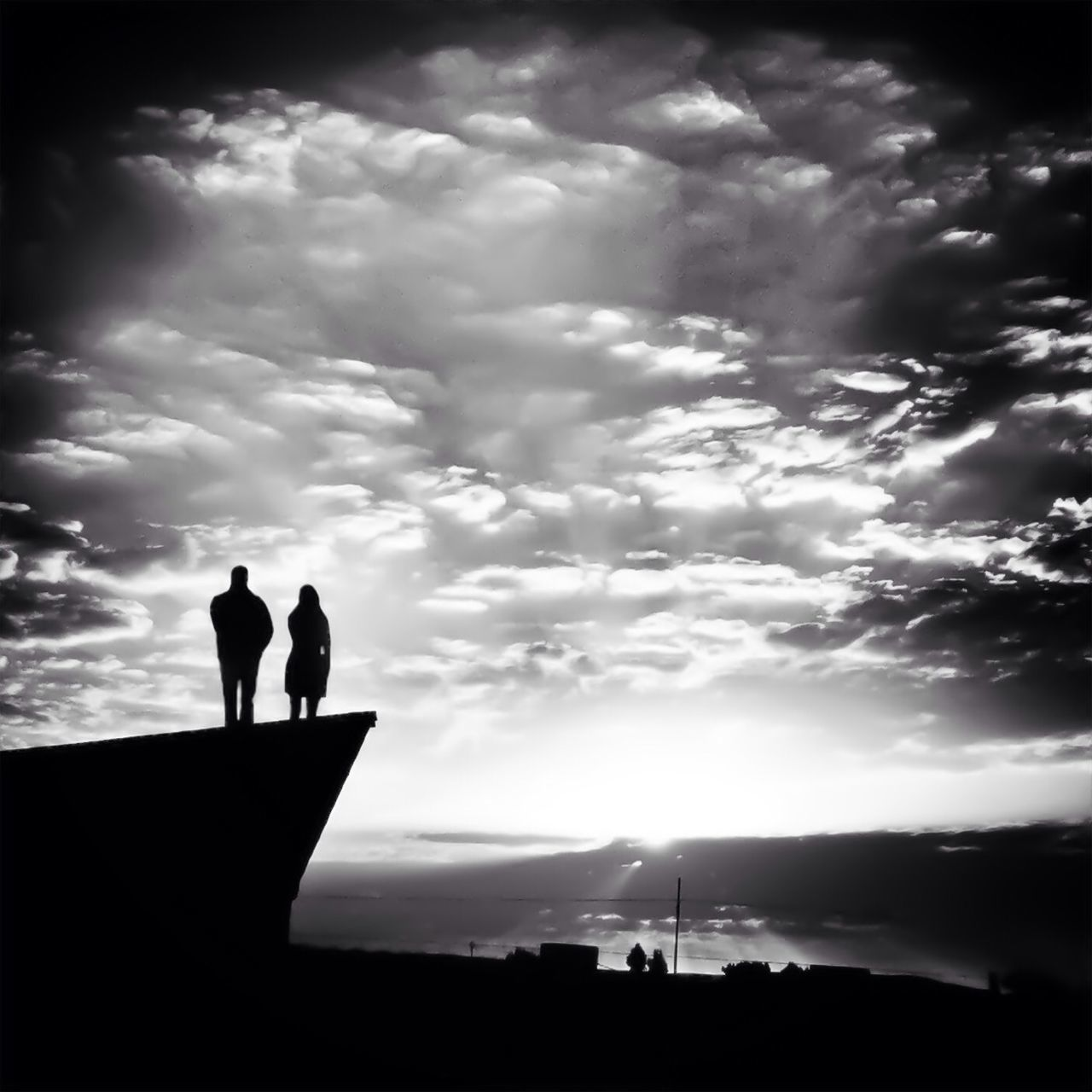 Rear View Of Silhouette People Standing On Retaining Wall Against Cloudy Sky