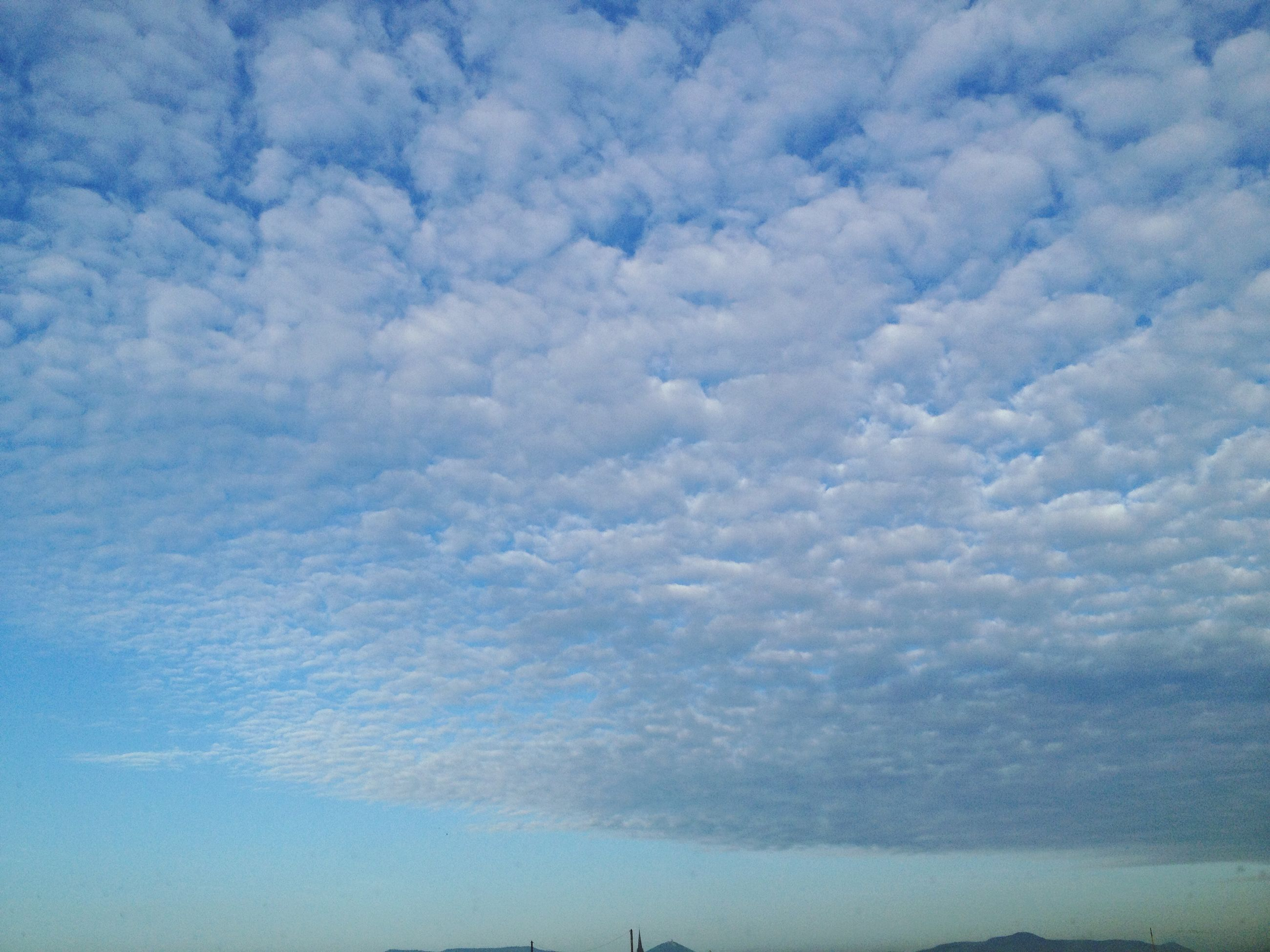 sky, cloud - sky, low angle view, cloudy, beauty in nature, tranquility, blue, scenics, tranquil scene, nature, cloud, cloudscape, weather, outdoors, idyllic, silhouette, day, no people, overcast, sunlight