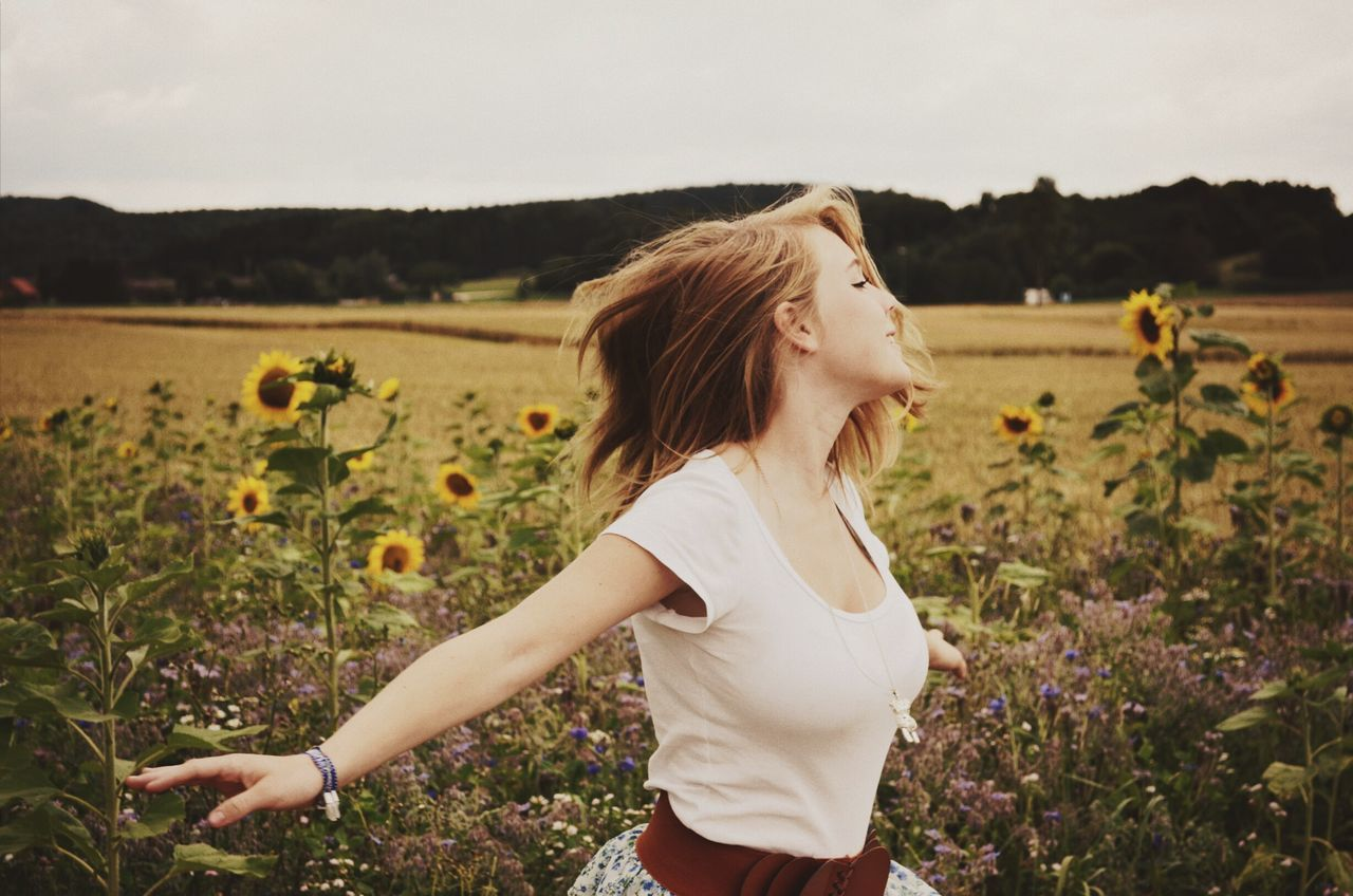 field, one person, growth, real people, nature, plant, sunflower, flower, casual clothing, young women, agriculture, outdoors, standing, beauty in nature, landscape, day, women, lifestyles, rural scene, beautiful woman, sky, young adult, tree, freshness, people