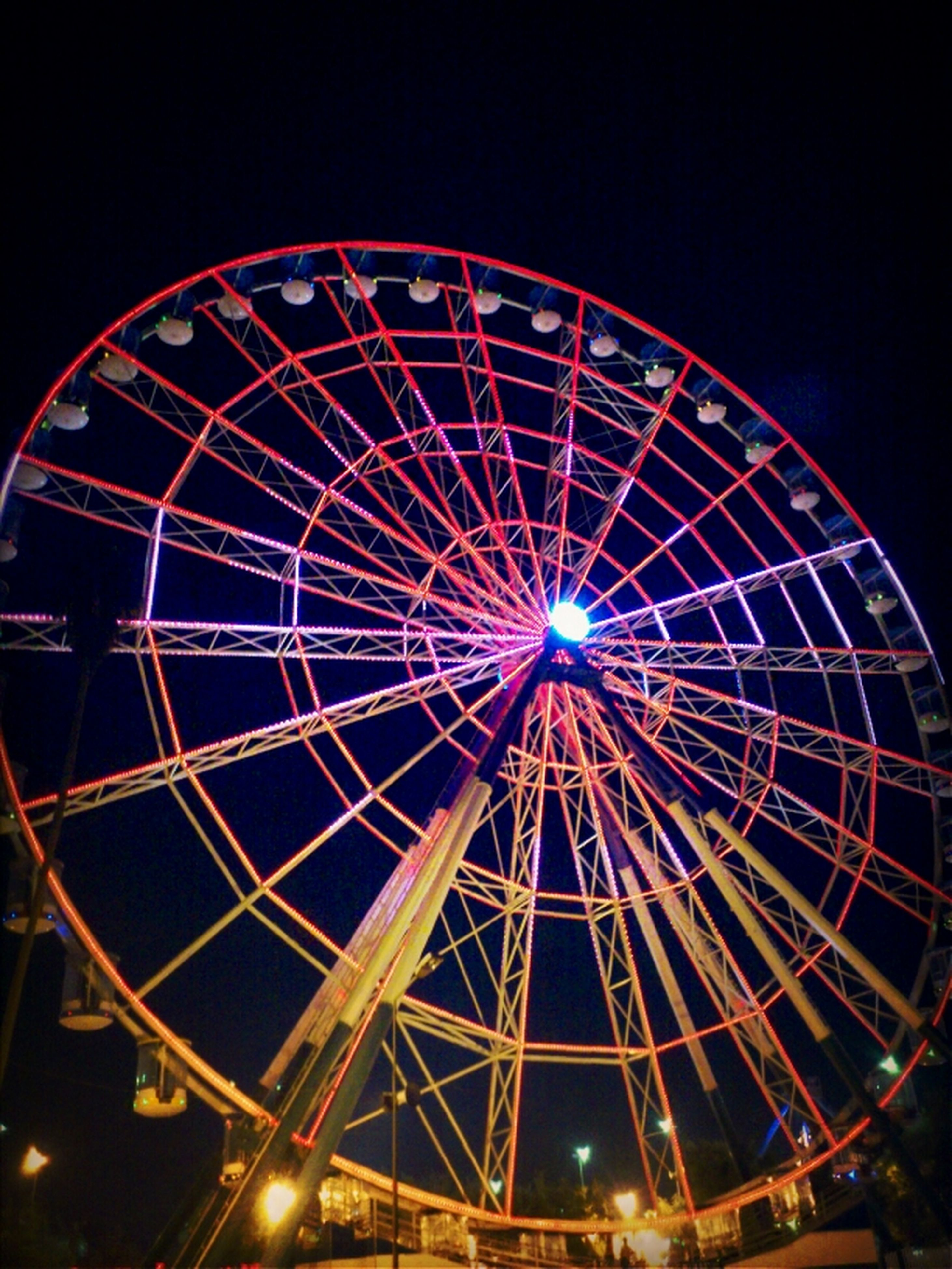 amusement park ride, amusement park, ferris wheel, arts culture and entertainment, low angle view, illuminated, night, sky, circle, fun, big wheel, enjoyment, multi colored, large, clear sky, built structure, outdoors, traveling carnival, geometric shape, no people
