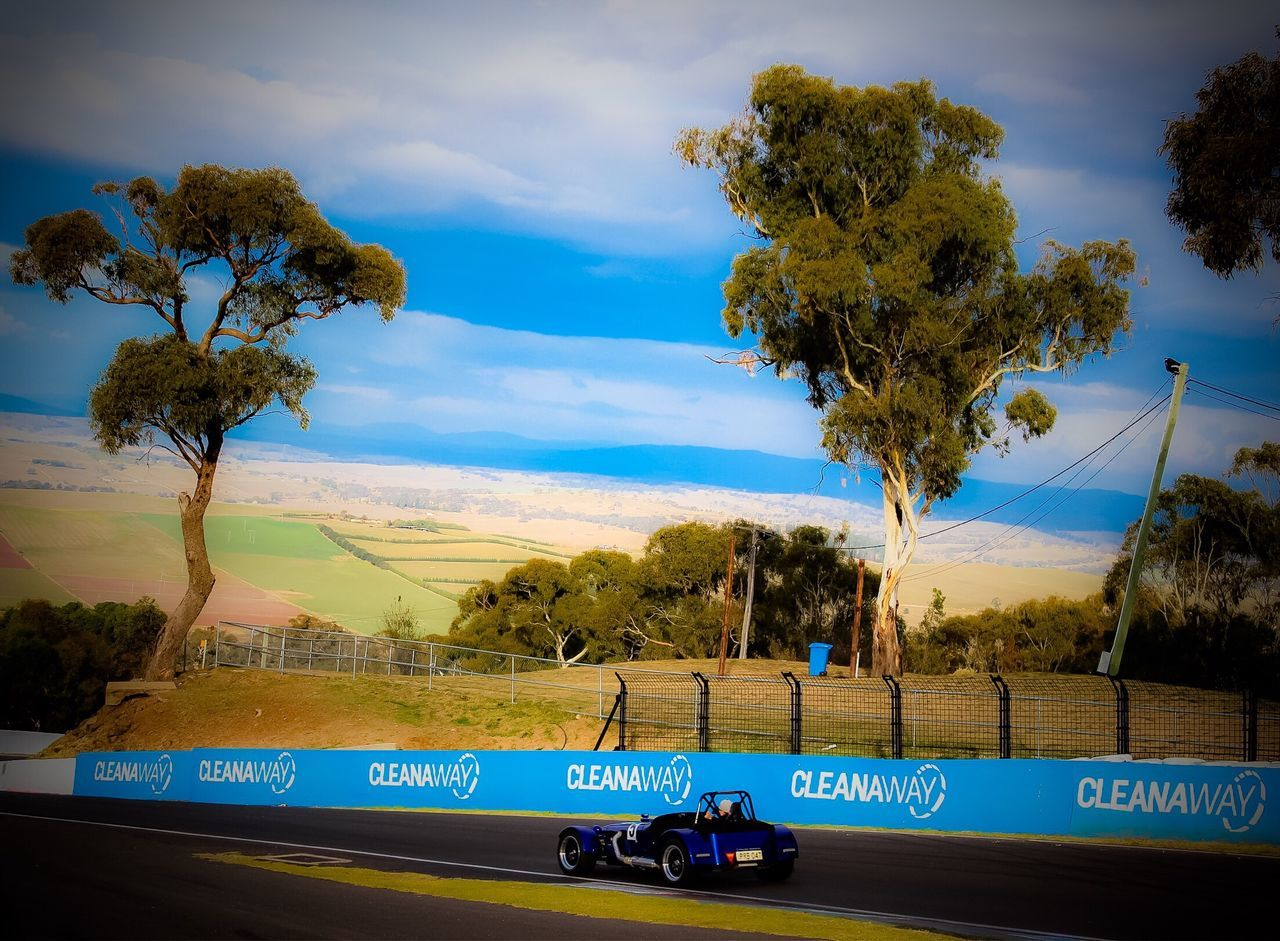 Mount Panorama Race Track Vintage Car Race Track Public Road Western Script Text Tree Sky Communication Cloud - Sky Land Vehicle Day Transportation Road No People Growth Outdoors Road Sign Nature Landscape_Collection Sports Venue Motorsport Sports Cars