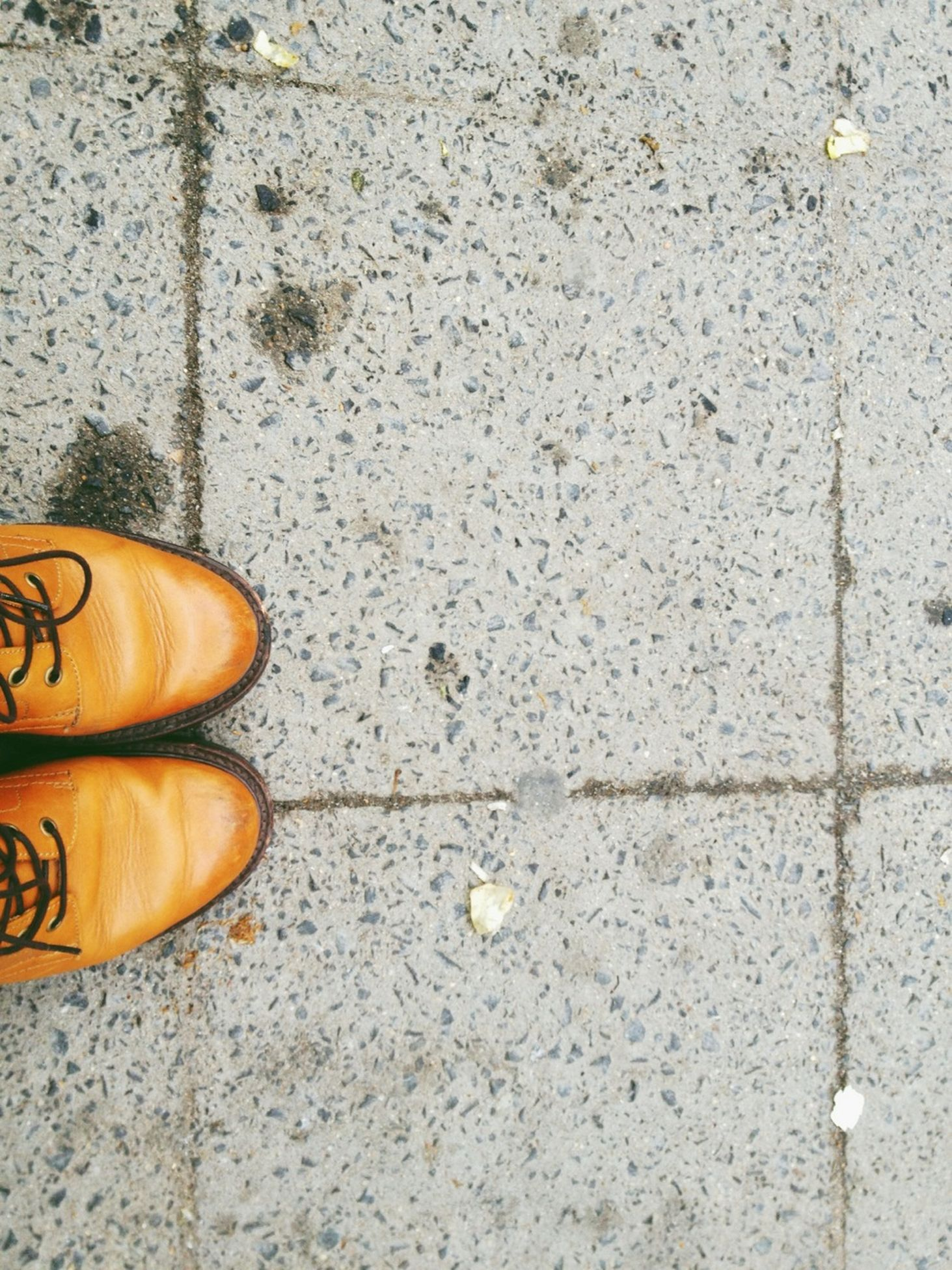 shoe, low section, footwear, person, high angle view, street, one person, pair, cobblestone, personal perspective, human foot, close-up, sidewalk, part of, directly above, yellow, outdoors, paving stone, day
