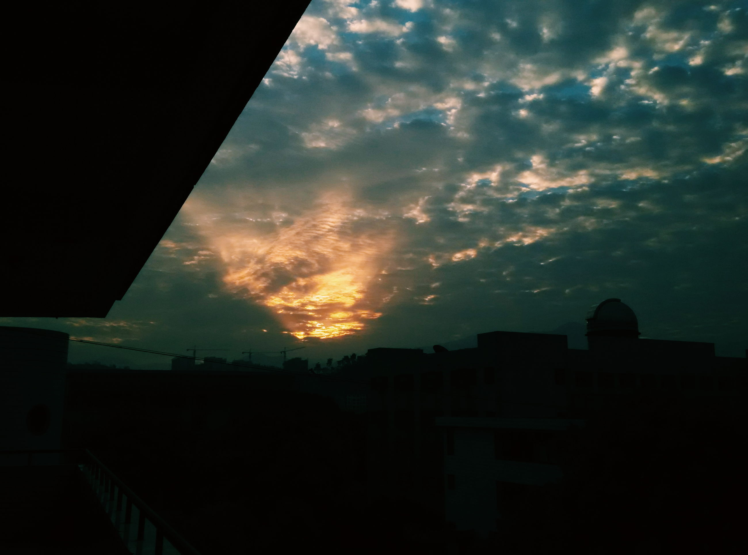 sunset, silhouette, architecture, built structure, building exterior, sky, cloud - sky, orange color, dark, low angle view, building, house, residential structure, cloud, residential building, city, cloudy, outdoors, nature, dramatic sky