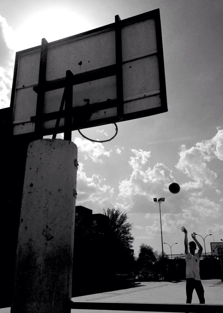 Basketball Hoop Cloud - Sky Sky Basketball - Sport Basketball Low Angle View Real People Outdoors One Person Day Leisure Activity Court Playing Silhouette Men Ball Basketball Player Building Exterior Road Sign