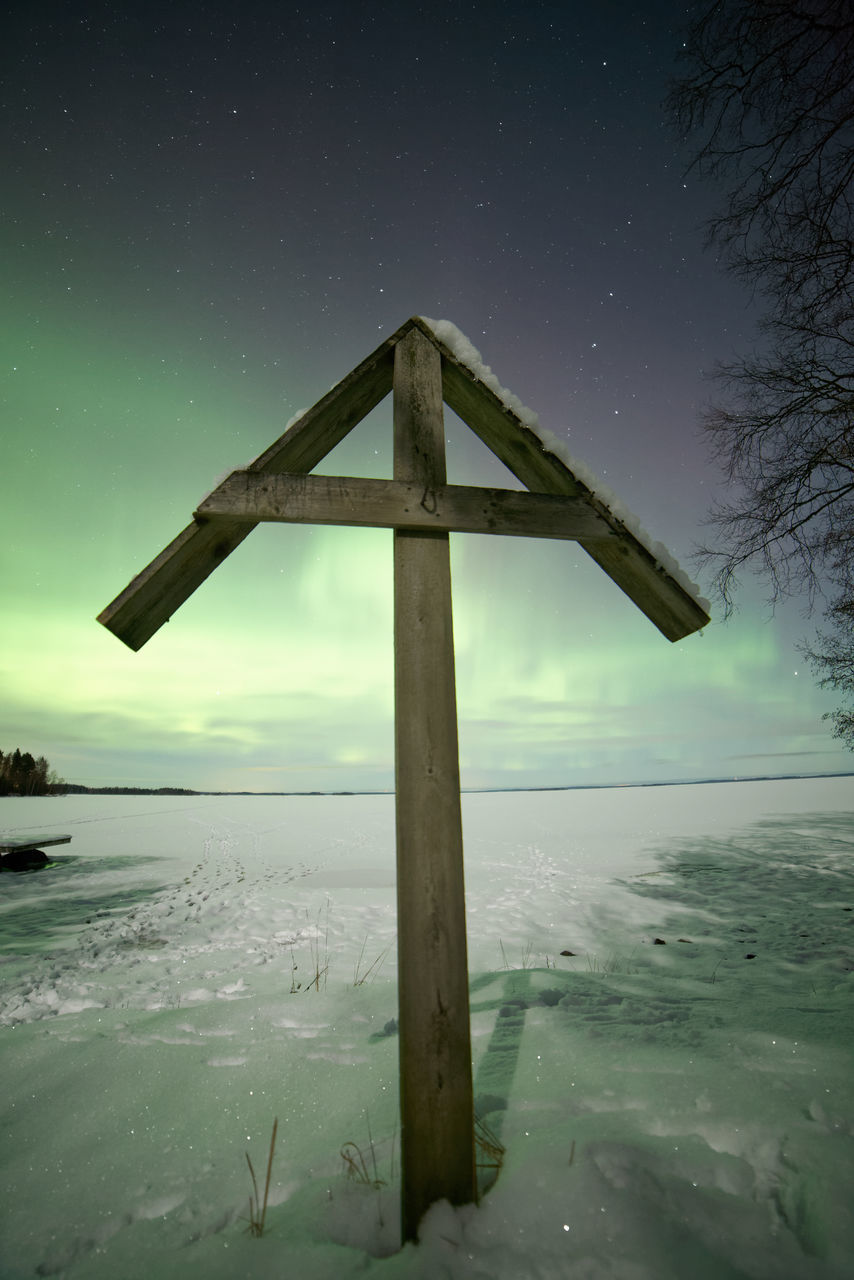 Wooden Structure On Snow Covered Field Against Aurora Borealis At Night
