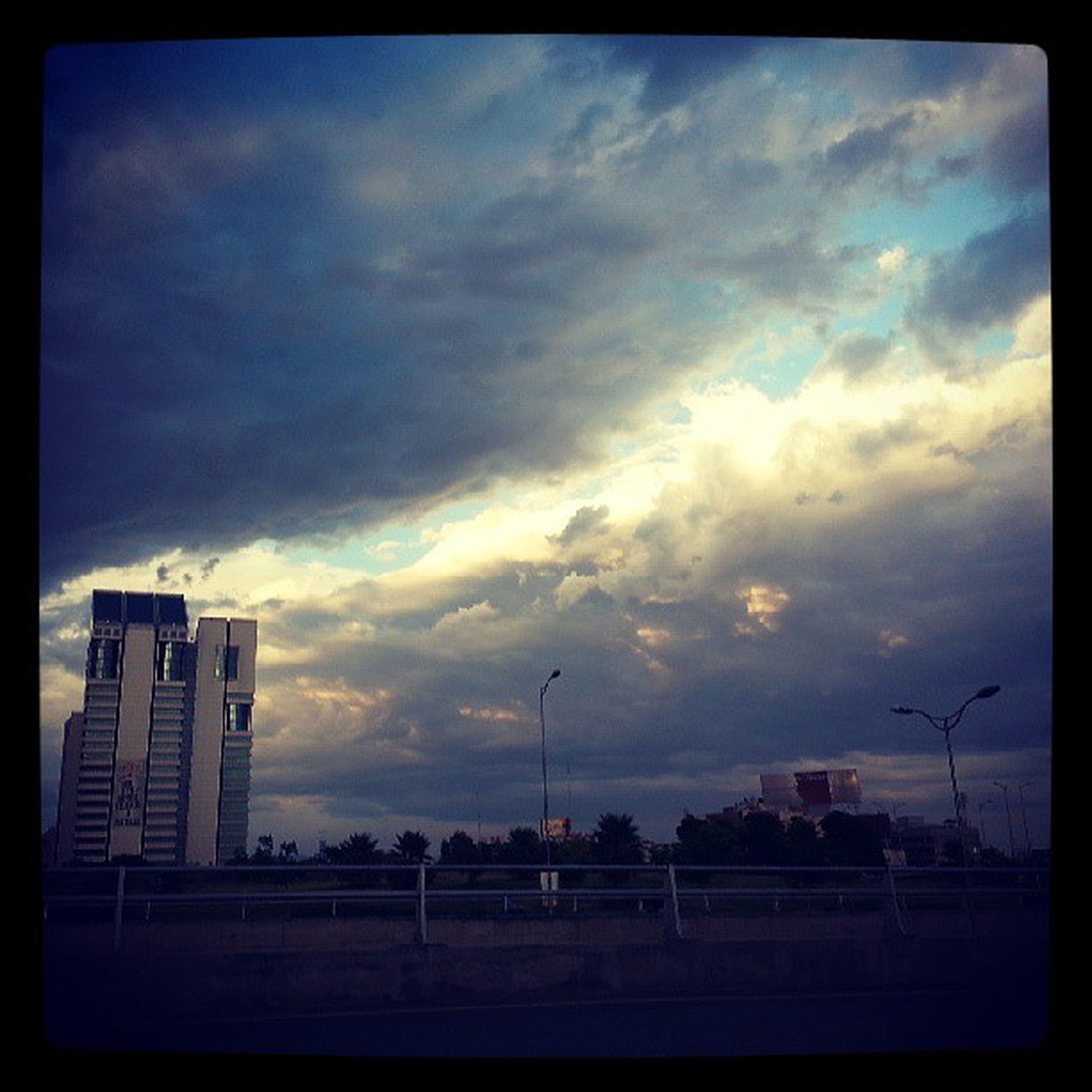 sky, cloud - sky, transfer print, cloudy, auto post production filter, building exterior, built structure, cloud, architecture, overcast, transportation, weather, street light, city, dusk, fence, outdoors, nature, silhouette, sunset