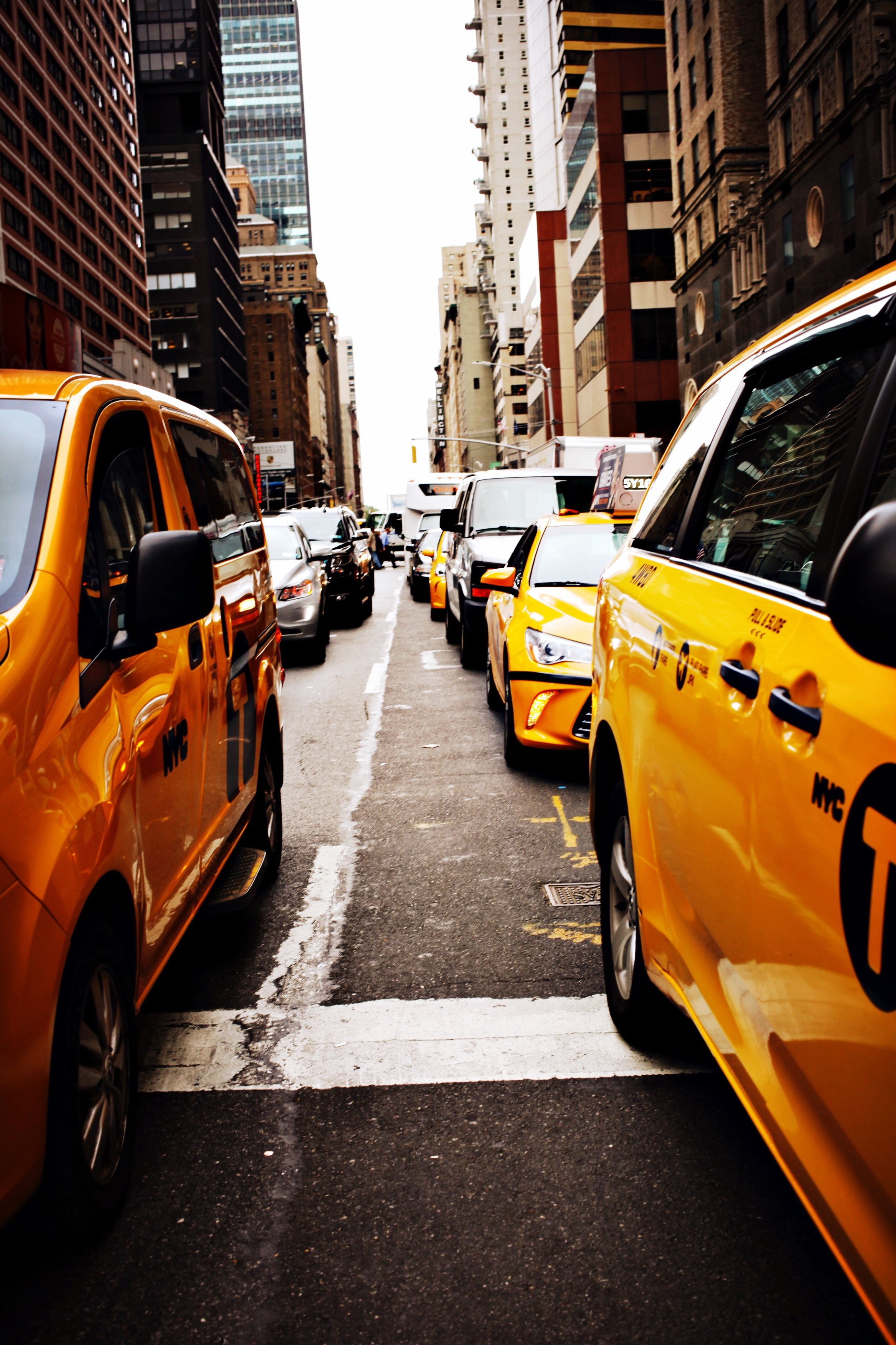 car, mode of transport, transportation, land vehicle, city, architecture, built structure, building exterior, street, road, city life, taxi, city street, road marking, yellow, yellow taxi, rush hour, outdoors, skyscraper, day, office building, busy