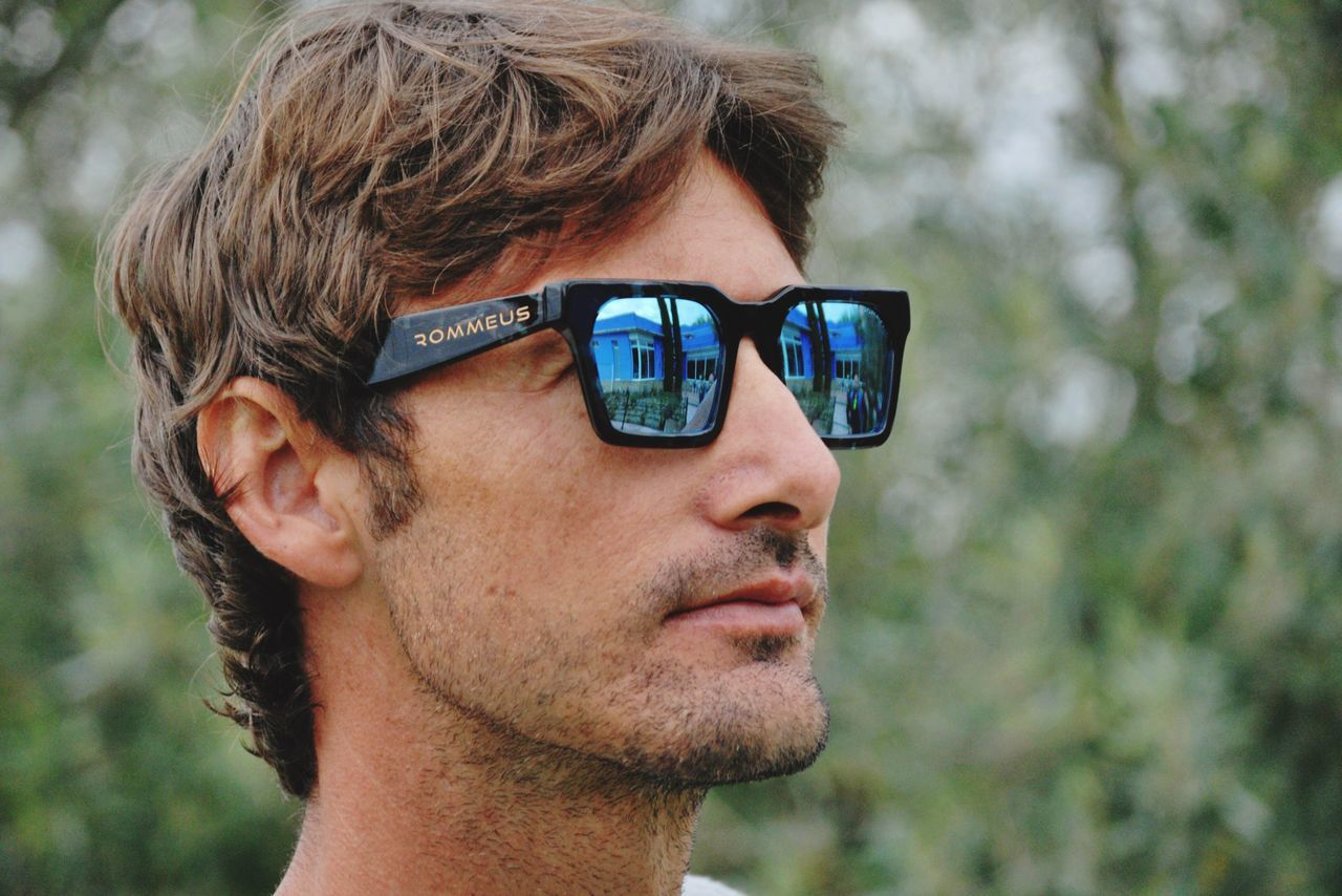 real people, mid adult men, sunglasses, mid adult, one person, focus on foreground, leisure activity, young adult, lifestyles, smiling, day, technology, beard, outdoors, portrait, young men, close-up, headshot, happiness, looking at camera, nature