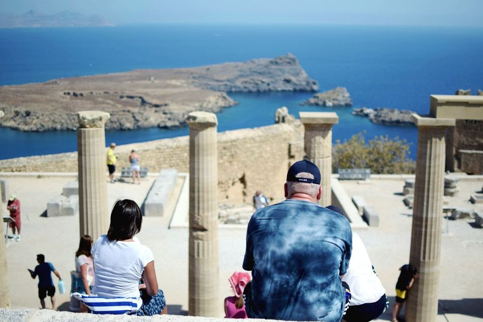 Enjoying the view. Rear View Real People Sea Lifestyles Men Built Structure Day Outdoors Sky Water Leisure Activity Building Exterior Women Architecture Beach Tourist Attraction  Greece Rhodos EyeEm Diversity