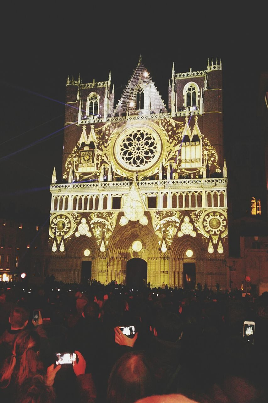 large group of people, religion, spirituality, architecture, place of worship, built structure, building exterior, night, real people, illuminated, statue, lifestyles, women, men, outdoors, sculpture, travel destinations, crowd, sky, people