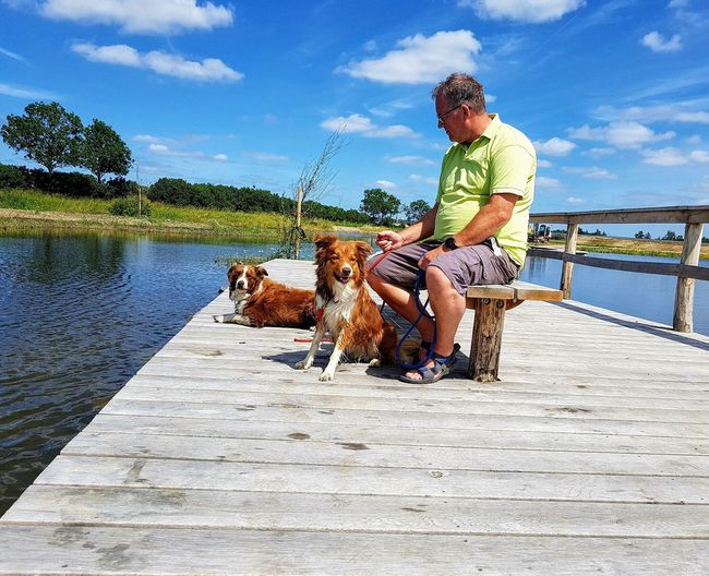 Second Acts Dog Day One Person Water Sky Only Men Outdoors Casual Clothing Adult Nature Cloud - Sky Nature Blue Sunlight Green Color Landscape Relaxing Time Insects Beautiful Nature A Peaceful Moment Water Reflections Water Surface Setting On A Bench