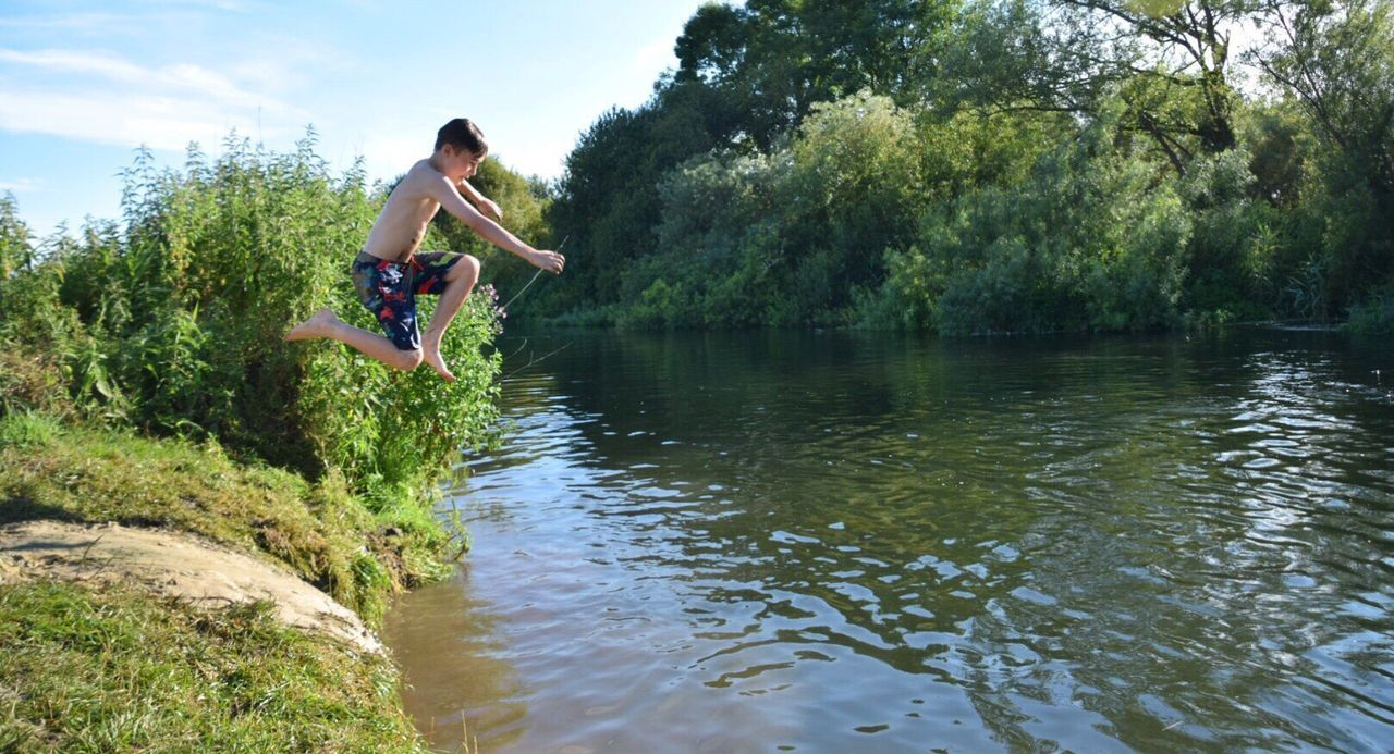 Water Fun Jumping Tree Mid-air Real People Full Length Wiltshire UK River Jumping River Fun One Person Enjoyment Motion River Boys Nature Outdoors Excitement Adventure Fun Family Time Freedom Hot Days River Swimming Childhood