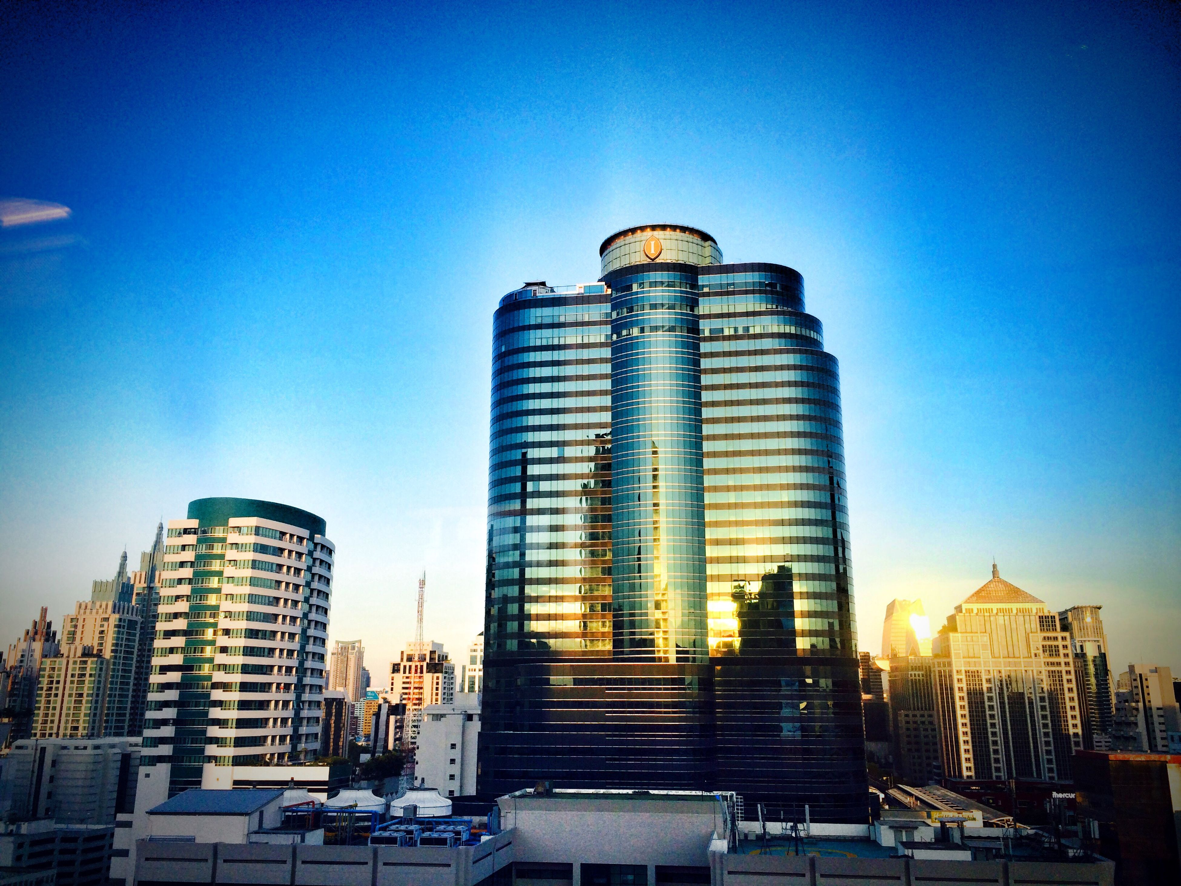 building exterior, architecture, built structure, clear sky, low angle view, blue, city, tall - high, tower, skyscraper, modern, illuminated, sunlight, sky, copy space, building, outdoors, office building, travel destinations, no people