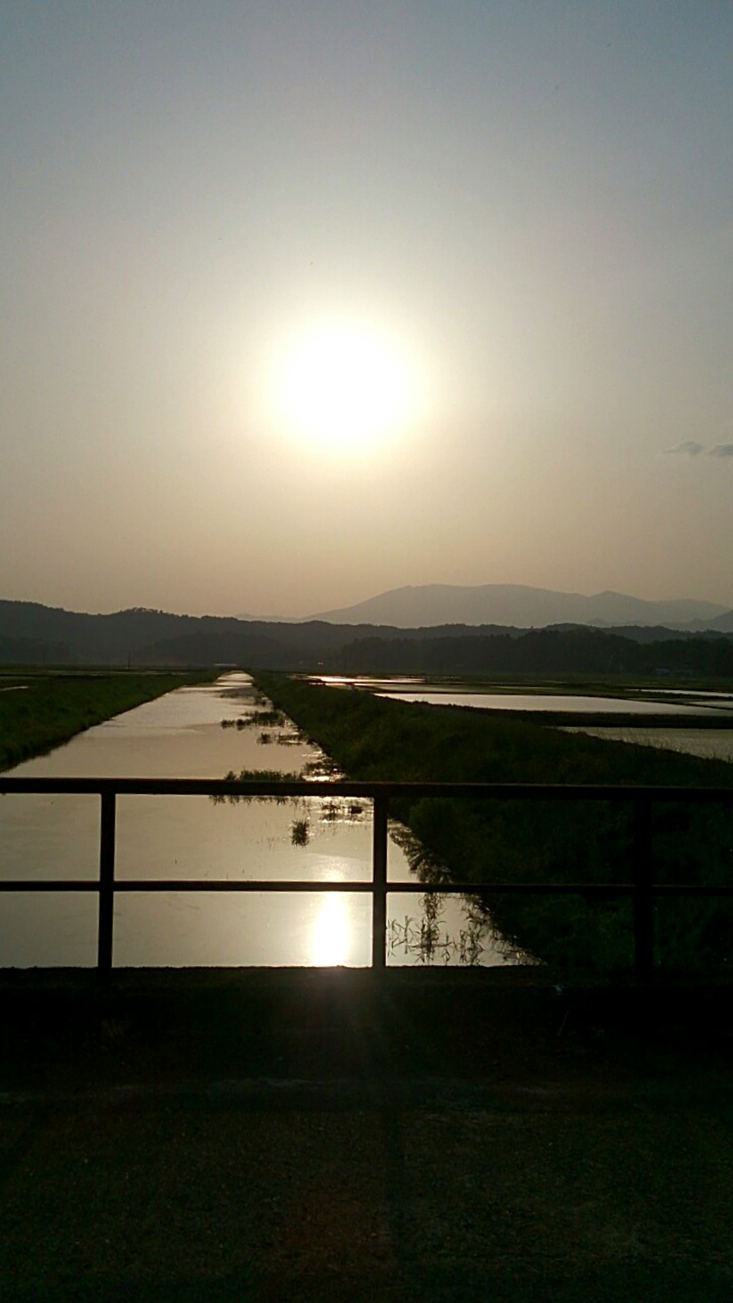 sun, tranquil scene, tranquility, scenics, water, sunset, beauty in nature, sunlight, railing, clear sky, nature, landscape, lake, sky, idyllic, copy space, grass, river, field, mountain