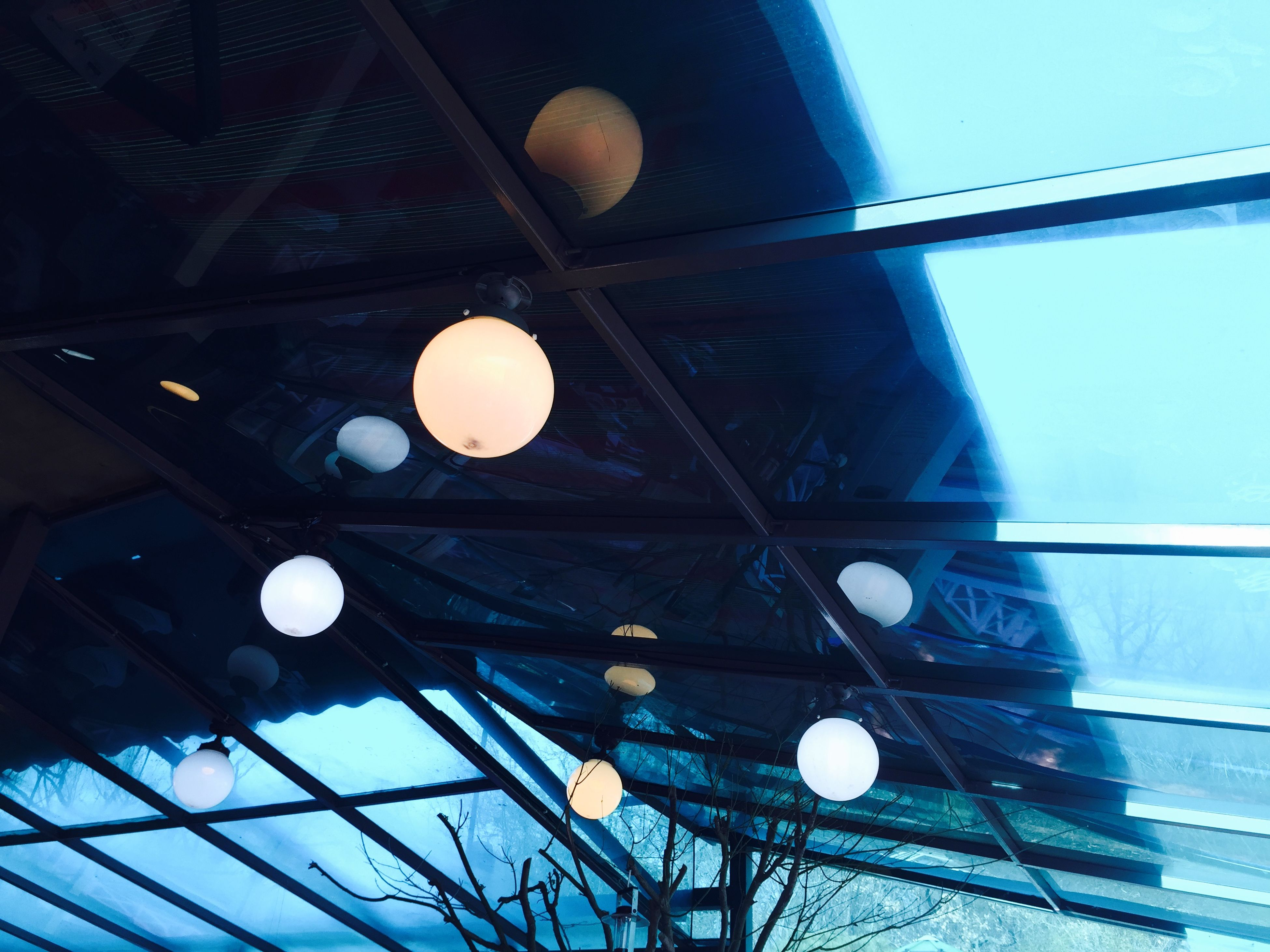 low angle view, lighting equipment, illuminated, sky, hanging, electricity, built structure, ceiling, architecture, light bulb, blue, electric light, moon, night, decoration, sphere, electric lamp, indoors, no people, street light
