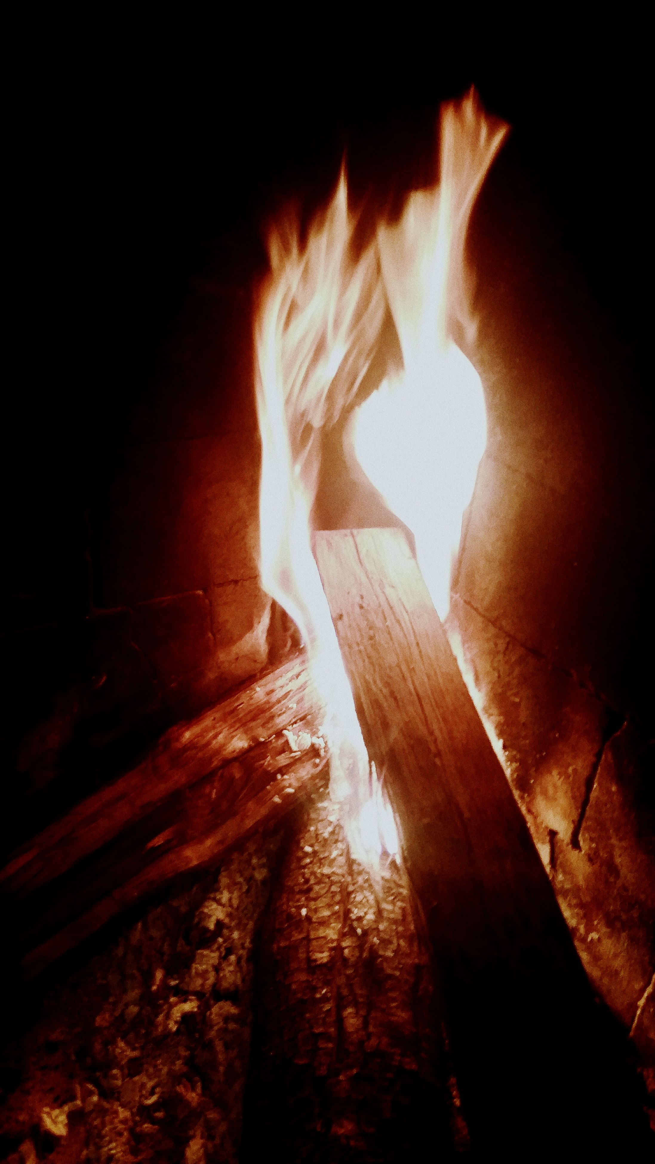 indoors, illuminated, flame, burning, night, fire - natural phenomenon, heat - temperature, glowing, light - natural phenomenon, dark, low angle view, wall - building feature, wood - material, sunlight, no people, close-up, darkroom, shadow, lit, lighting equipment