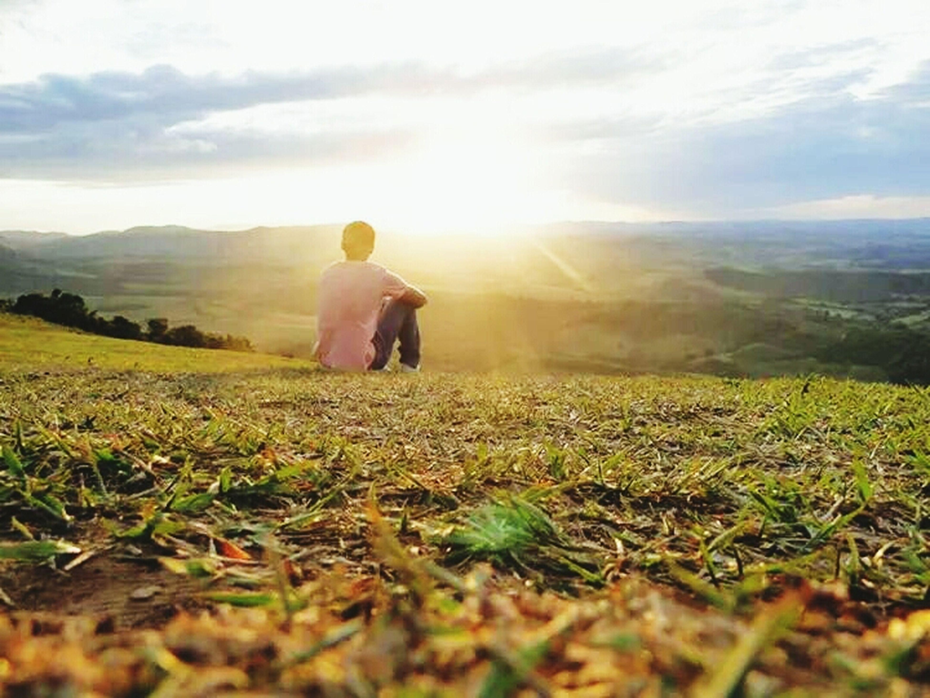 landscape, field, sun, sunbeam, grass, sky, sunlight, nature, lens flare, tranquil scene, beauty in nature, leisure activity, men, tranquility, scenics, lifestyles, mountain, rural scene, rear view