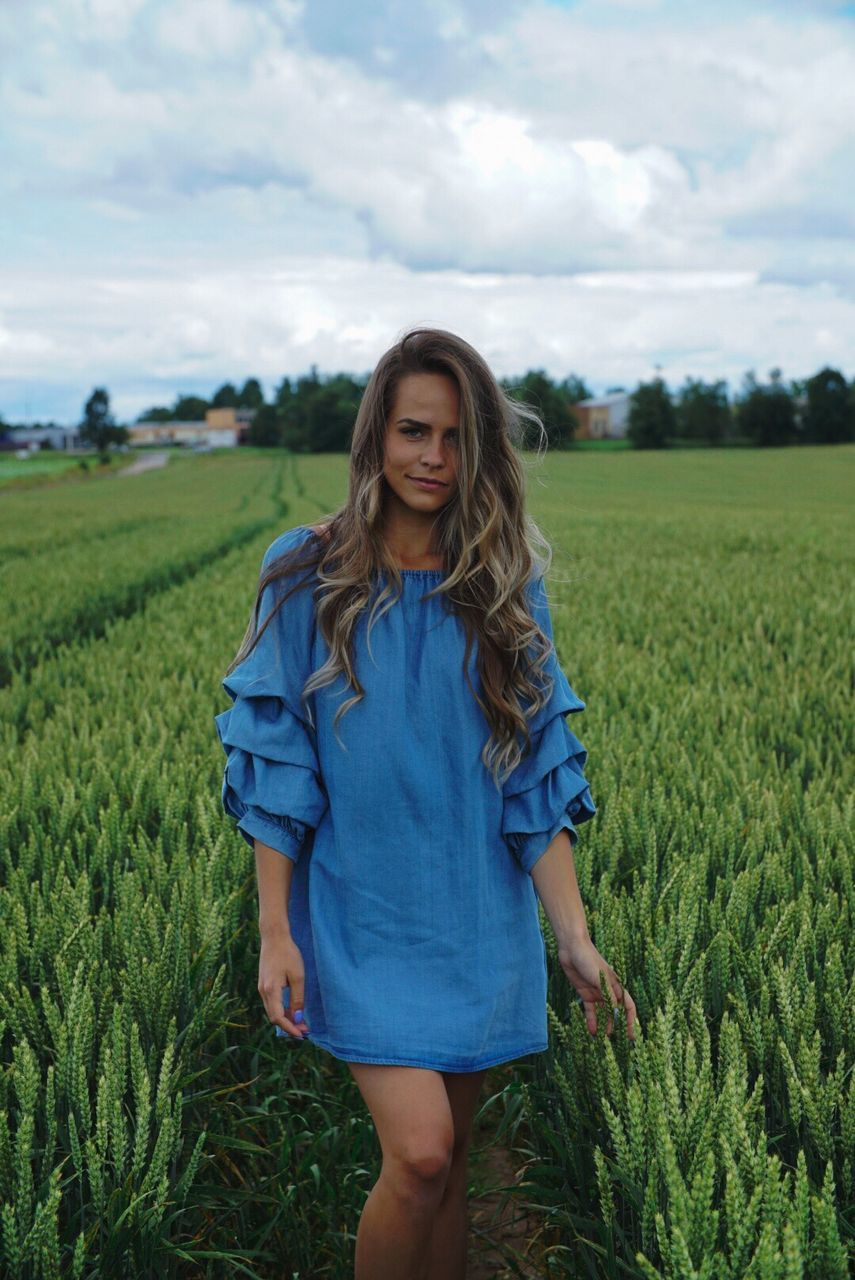 field, real people, sky, cloud - sky, one person, front view, nature, farm, agriculture, young adult, landscape, rural scene, day, growth, outdoors, young women, standing, casual clothing, beautiful woman, long hair, grass, leisure activity, portrait, looking at camera, green color, lifestyles, blue, beauty in nature, scenics, cereal plant, people