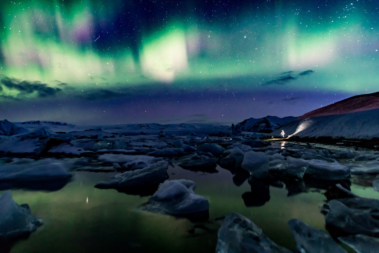"""Glacier lagoon. Such an experience to stand there in the night. Guided by the green, purple and whites of the aurora. Sounds of cracking and screeching ice around you. Jökulsárlón is alive. And we are in the mouth of the greatest glacier of Europe, Vatnajökull, as she spits her ice into the ocean. Even the massive Vatnajökull is melting faster and faster every year. Just like every glacier on our planet is disappearing, we are are letting the existence of our species slip through our hands. (Nikon D810 14-24mm f/2.8 ƒ/2.8 24mm 10"""" iso 1600) Astronomy Aurora Polaris Beauty In Nature Copy Space Ecology Glacier Ice Iceland Jökulsárlón Landscape Landscape_Collection Long Exposure Natgeo Natgeotravel Nature Night No People Outdoors Photographer Reflection Scandinavia Sky Space Vatnajökull Water"""