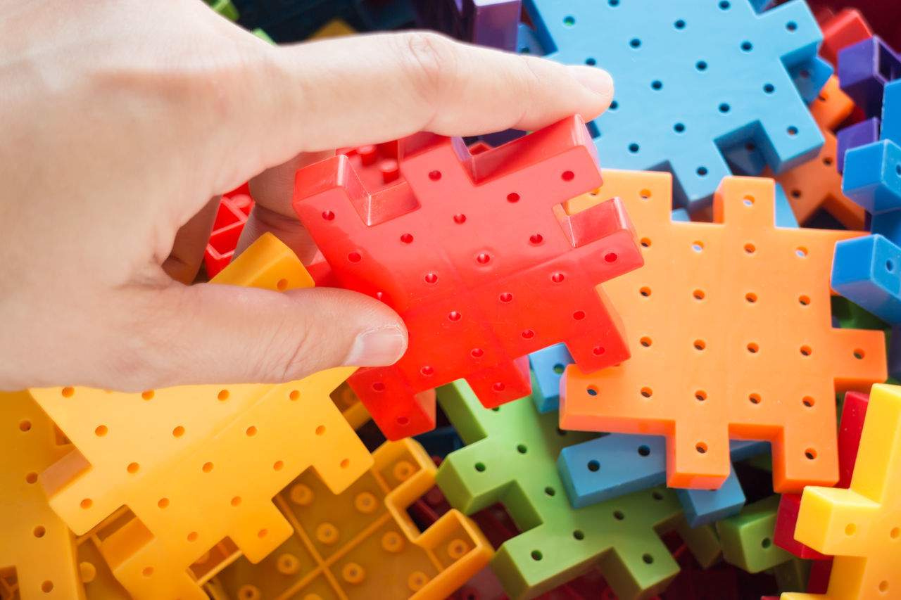 human hand, human body part, human finger, real people, leisure activity, one person, multi colored, playing, leisure games, toy, toy block, puzzle, indoors, large group of objects, gambling, holding, game, close-up, lifestyles, childhood, day, chance, dice