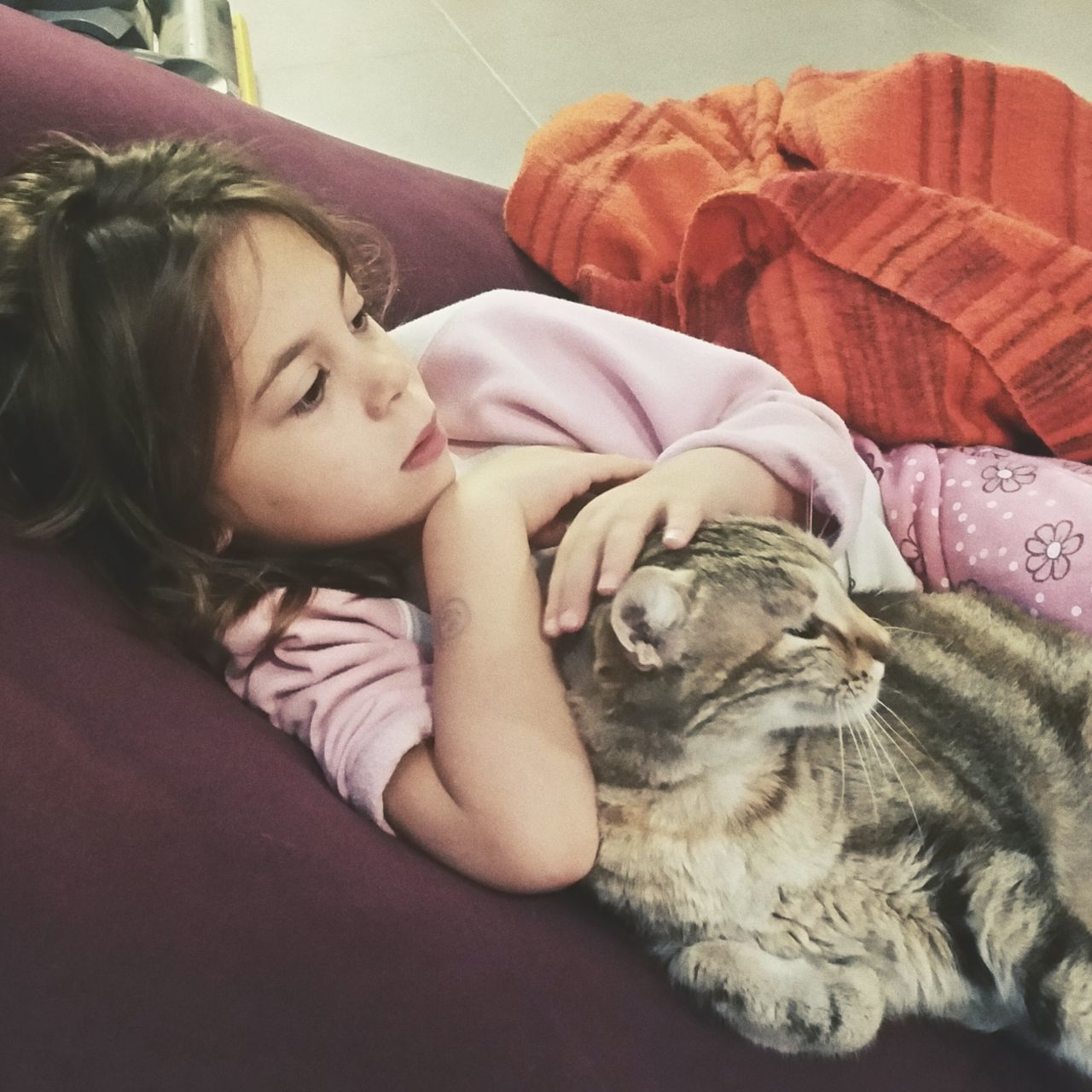 High Angle View Of Girl Relaxing With Cat On Sofa