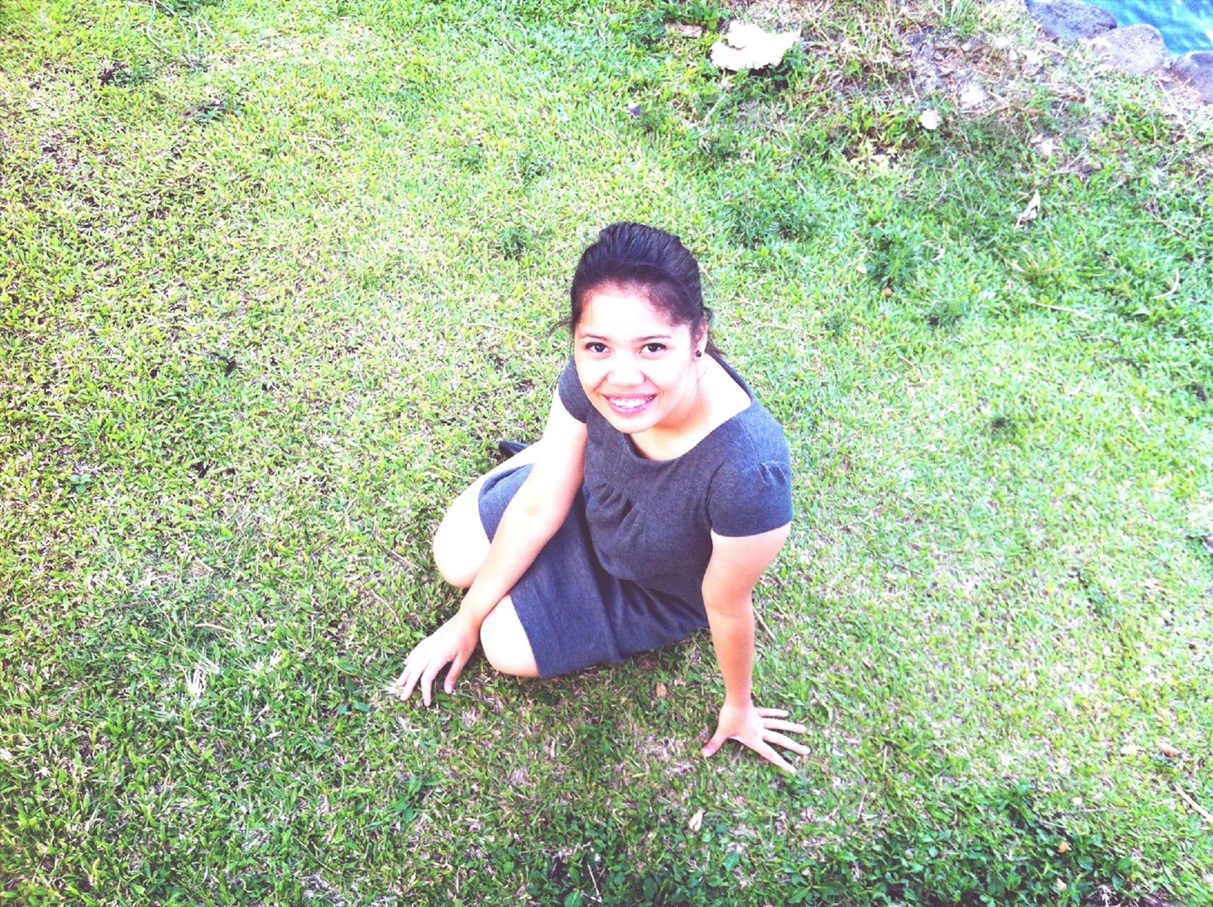 person, portrait, looking at camera, grass, lifestyles, leisure activity, casual clothing, high angle view, smiling, green color, front view, young adult, happiness, full length, standing, sitting, grassy, field