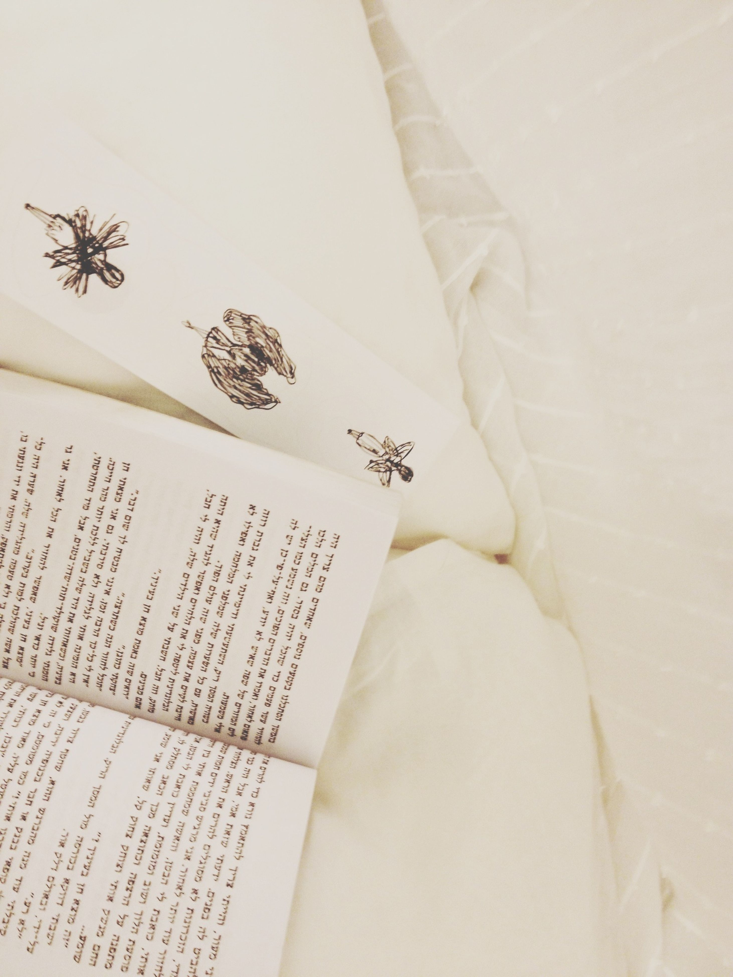 indoors, paper, book, text, high angle view, still life, communication, white color, table, education, white background, close-up, western script, home interior, bed, white, wall - building feature, no people, document, studio shot