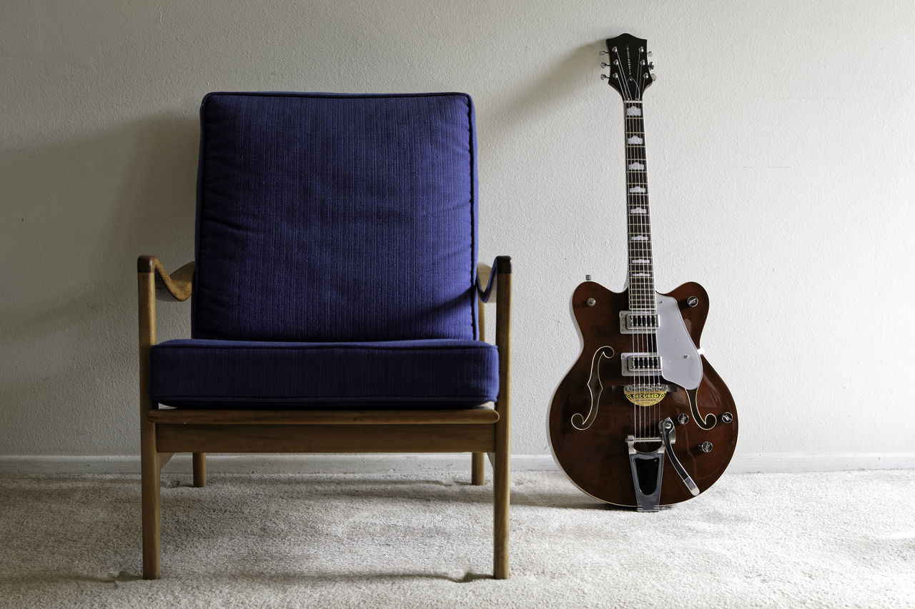 Electric guitar and vintage chair. Chair cushions electric guitar furniture guitar home interior indoors Lieblingsteil mid-century modern Music musical instrument no people Quality style vintage Wood