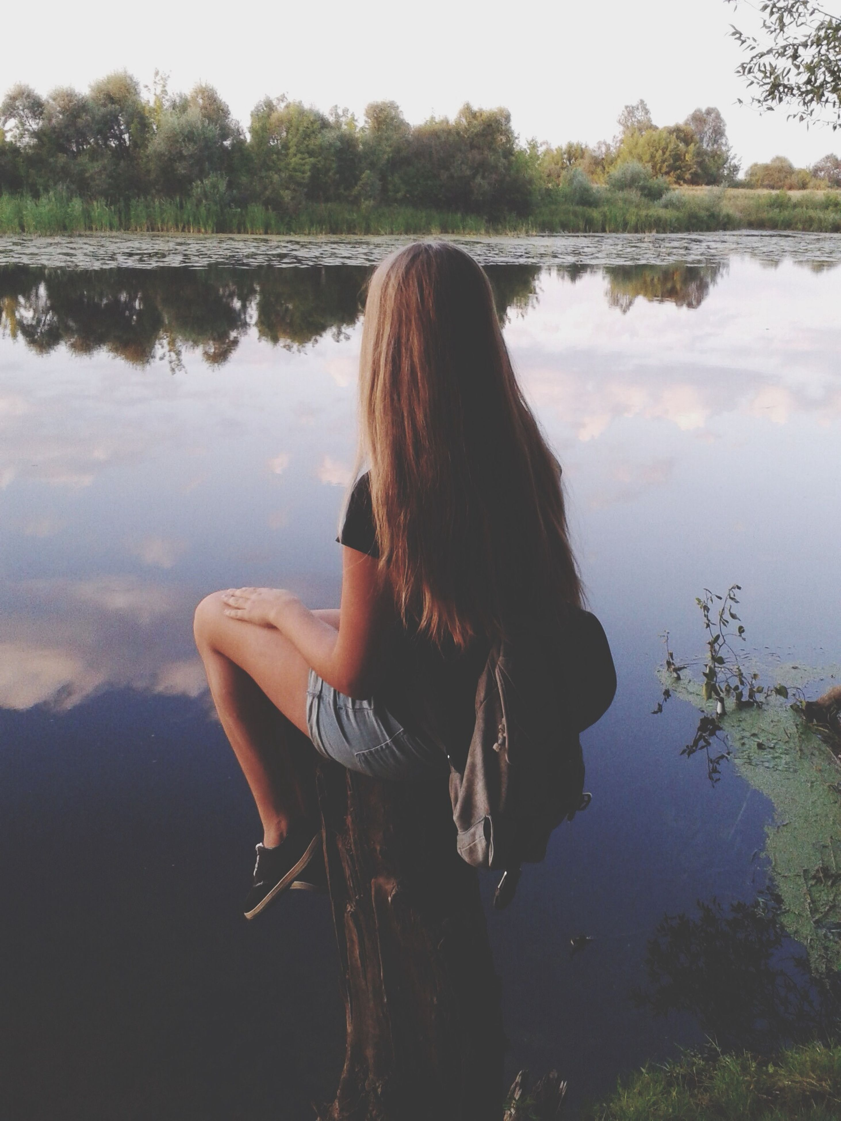 water, rear view, lake, leisure activity, lifestyles, long hair, reflection, tranquility, tree, nature, tranquil scene, standing, person, three quarter length, beauty in nature, waist up, casual clothing, side view