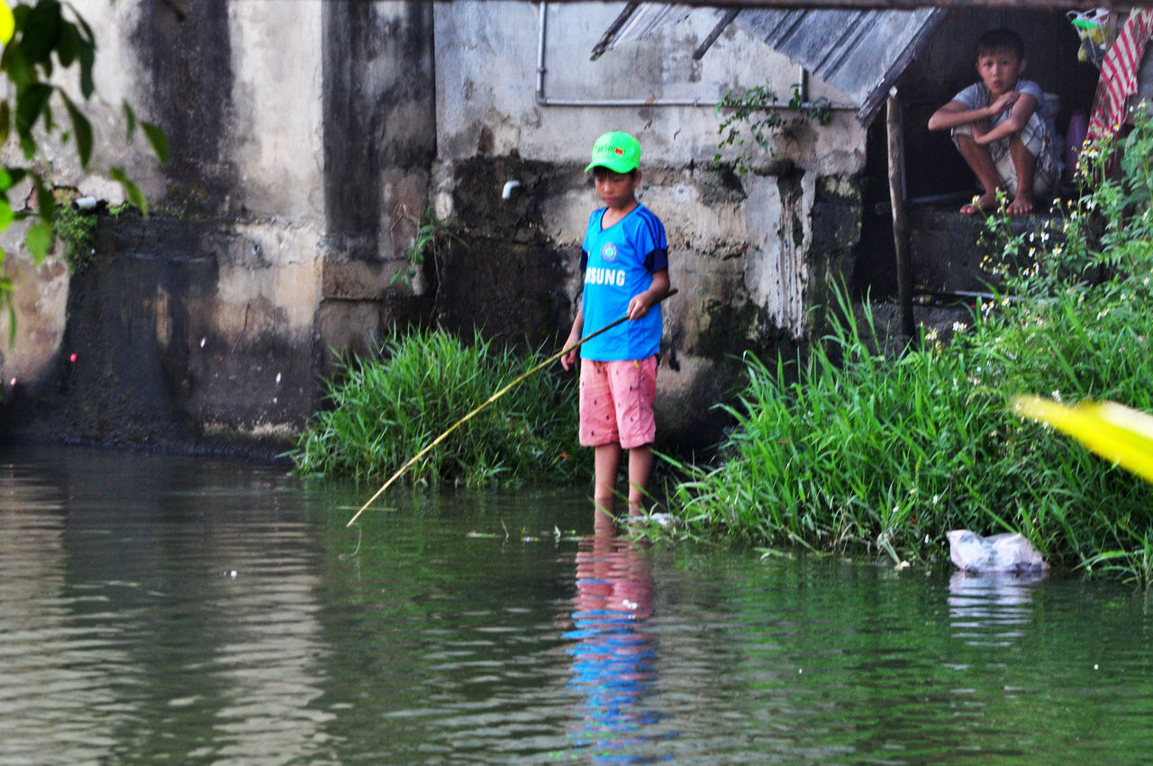 Boy fishing in stream outside backdoor of his home in a village near Hoi An, Vietnam. Boys Building Exterior Childhood Day Editorial  Fishing Fishing Rods Friends Hoi An Homes Lifestyles Outdoors Rivers Rural Streams Vietnam Villages Water