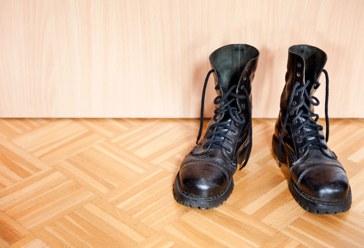 Pair of old used black bovver boots on parquet floor, objects in horizontal orientation, nobody. Army Army Boots Black Boot Boots Bovver Damaged Footgear Footwear Indoors  Lace Leather Military No People Old Pair Parquet Floor Shoe Shoe Shoes Steel-toe Used Worn