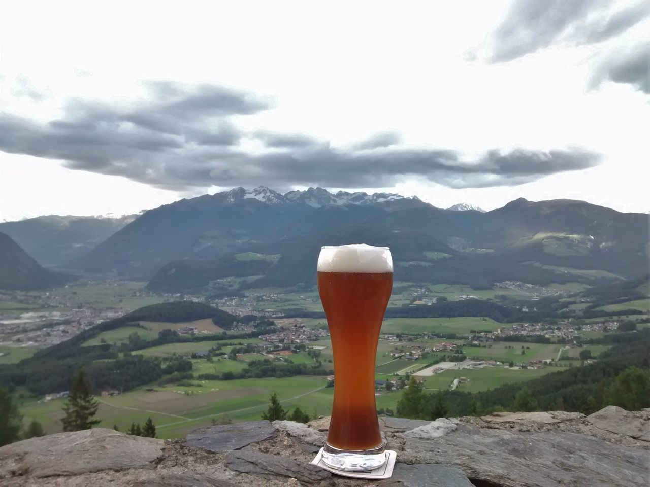 mountain, mountain range, nature, drink, landscape, beauty in nature, beer glass, no people, scenics, cold temperature, sky, alcohol, day, outdoors, freshness, frothy drink, tree, close-up