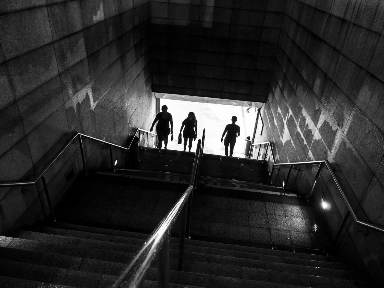 Silhouette of three people walking on the stairs of an underground passage at night B&w B&w Photography Black And White Blackandwhite City City Life Entering Looking Down Night People Railing Silhouette Silhouettes Staircase Steps Steps And Staircases Streetphotography Urban Urbanphotography Walking