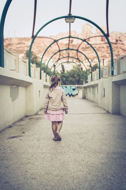 Alone Arch Architecture Bridge Casual Clothing Day Full Length Human Back Israel Little Girl Lonely One Girl Only One Person Outdoors Rear View Sad Sky Stone Wall Street Walking Wall Way