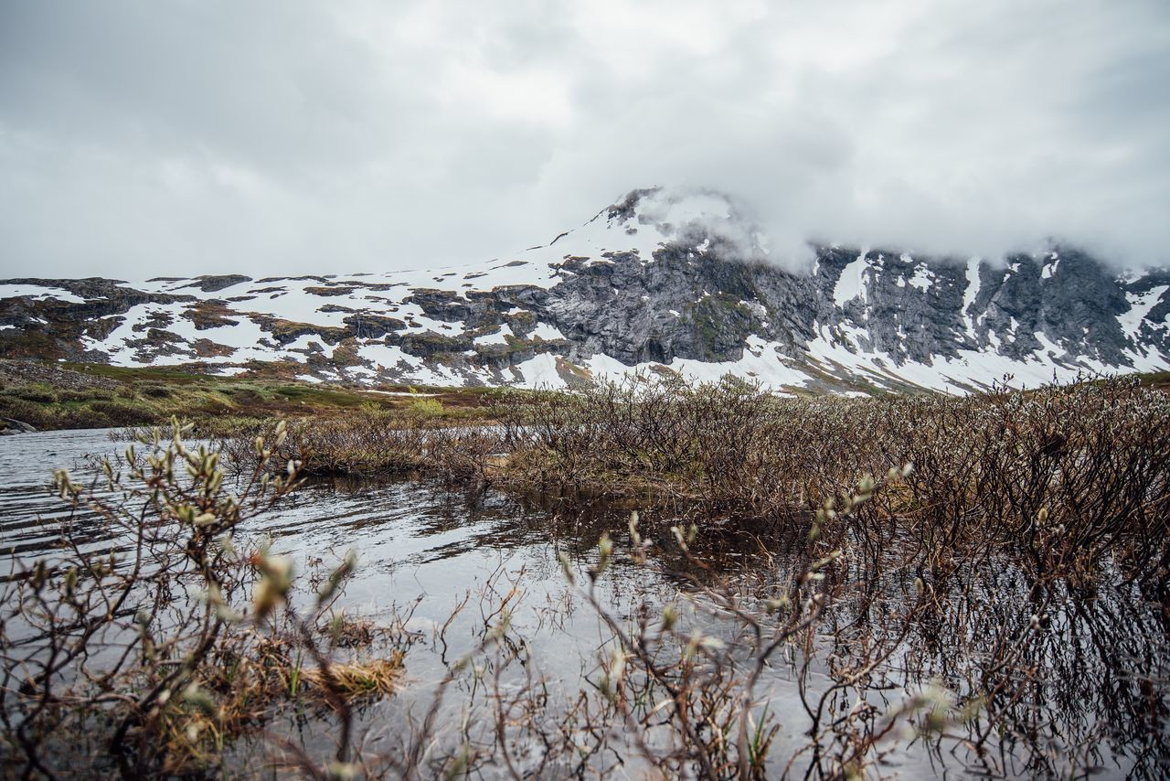 Stream By Snowcapped Mountain Against Cloudy Sky