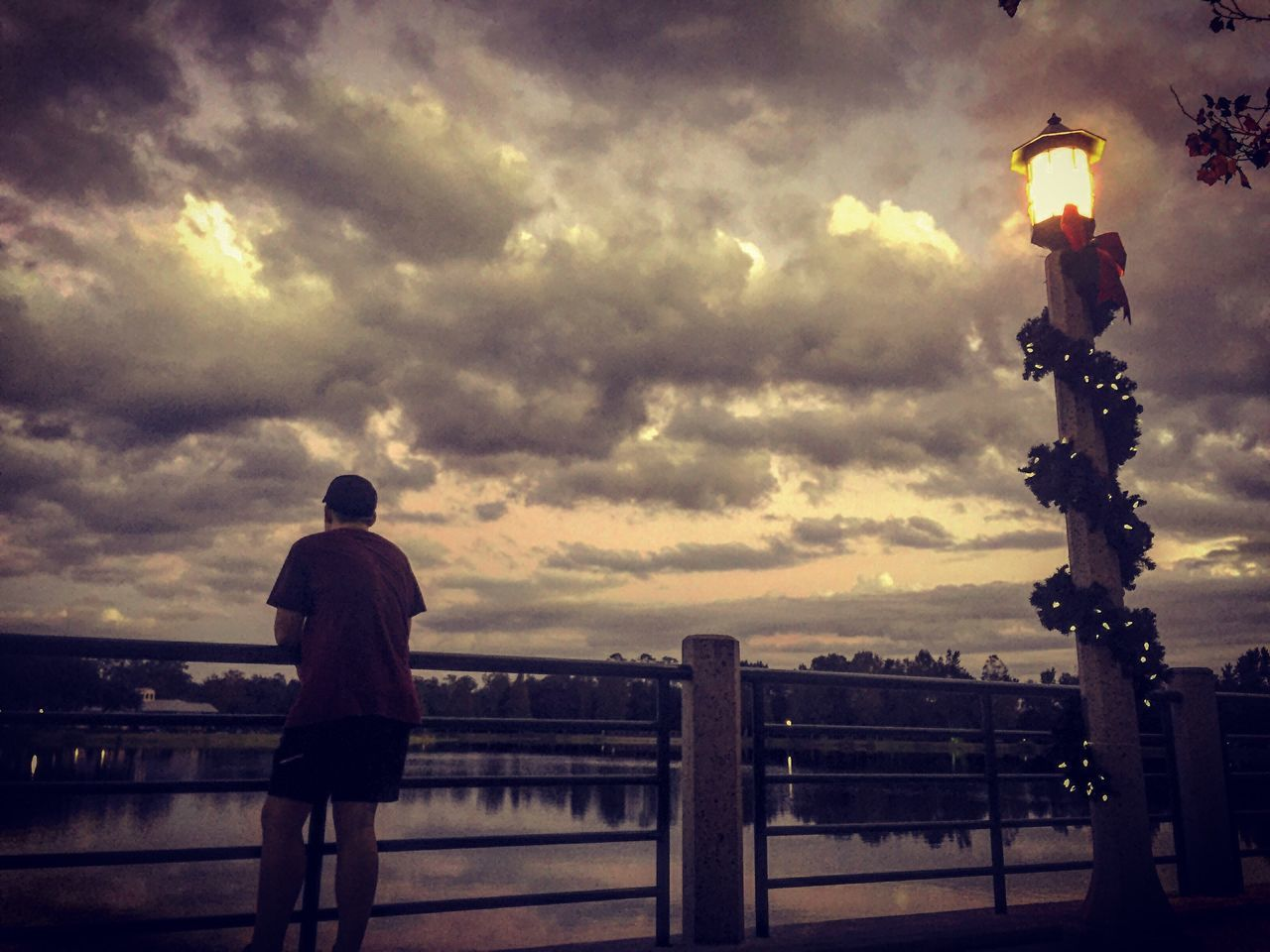 cloud - sky, sky, railing, dramatic sky, sunset, silhouette, rear view, outdoors, walking, men, real people, built structure, standing, full length, illuminated, architecture, storm cloud, day, nature, city, one person, people