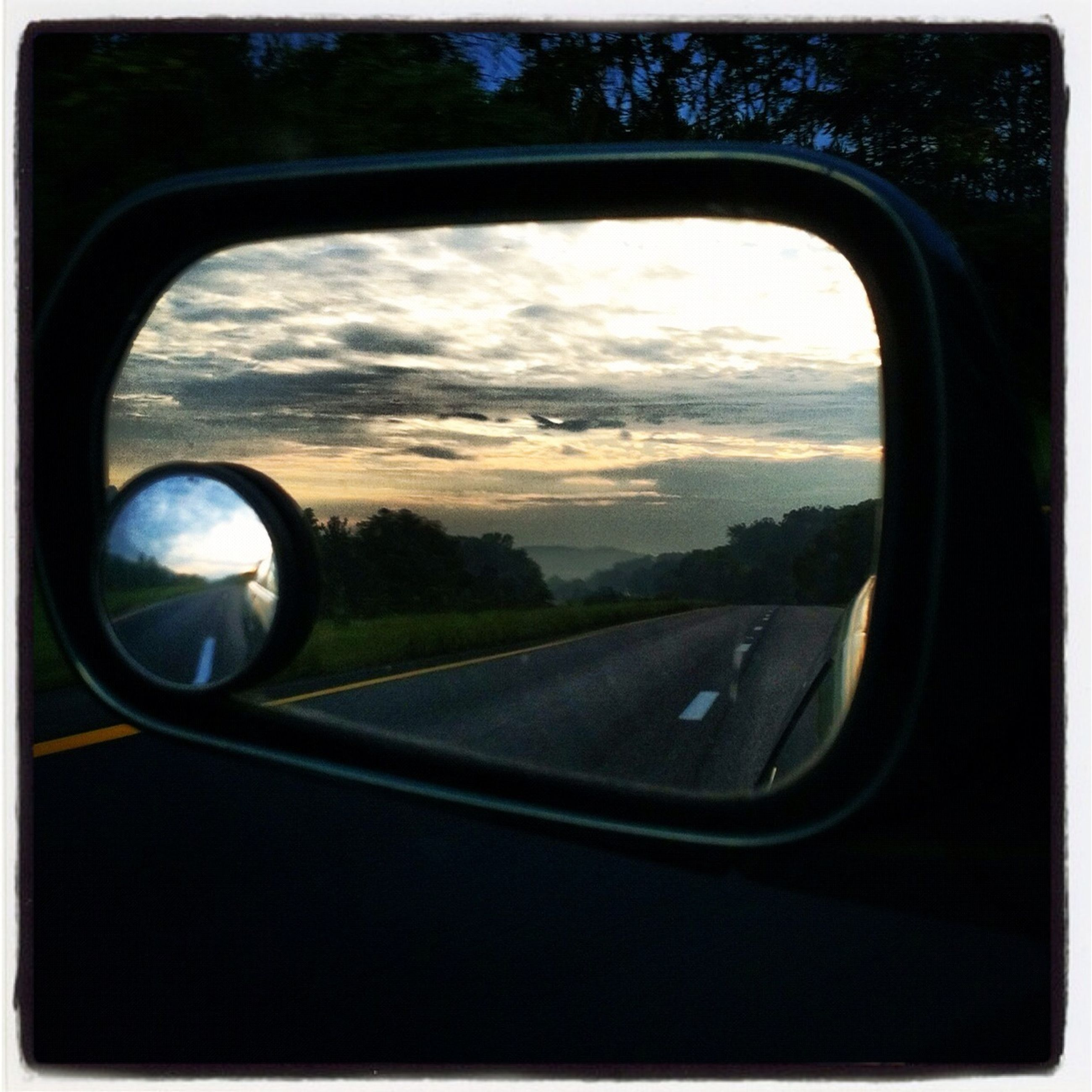 transportation, side-view mirror, sky, land vehicle, road, mode of transport, car, reflection, cloud - sky, circle, landscape, transparent, glass - material, close-up, cloud, street, part of, nature, tree, no people