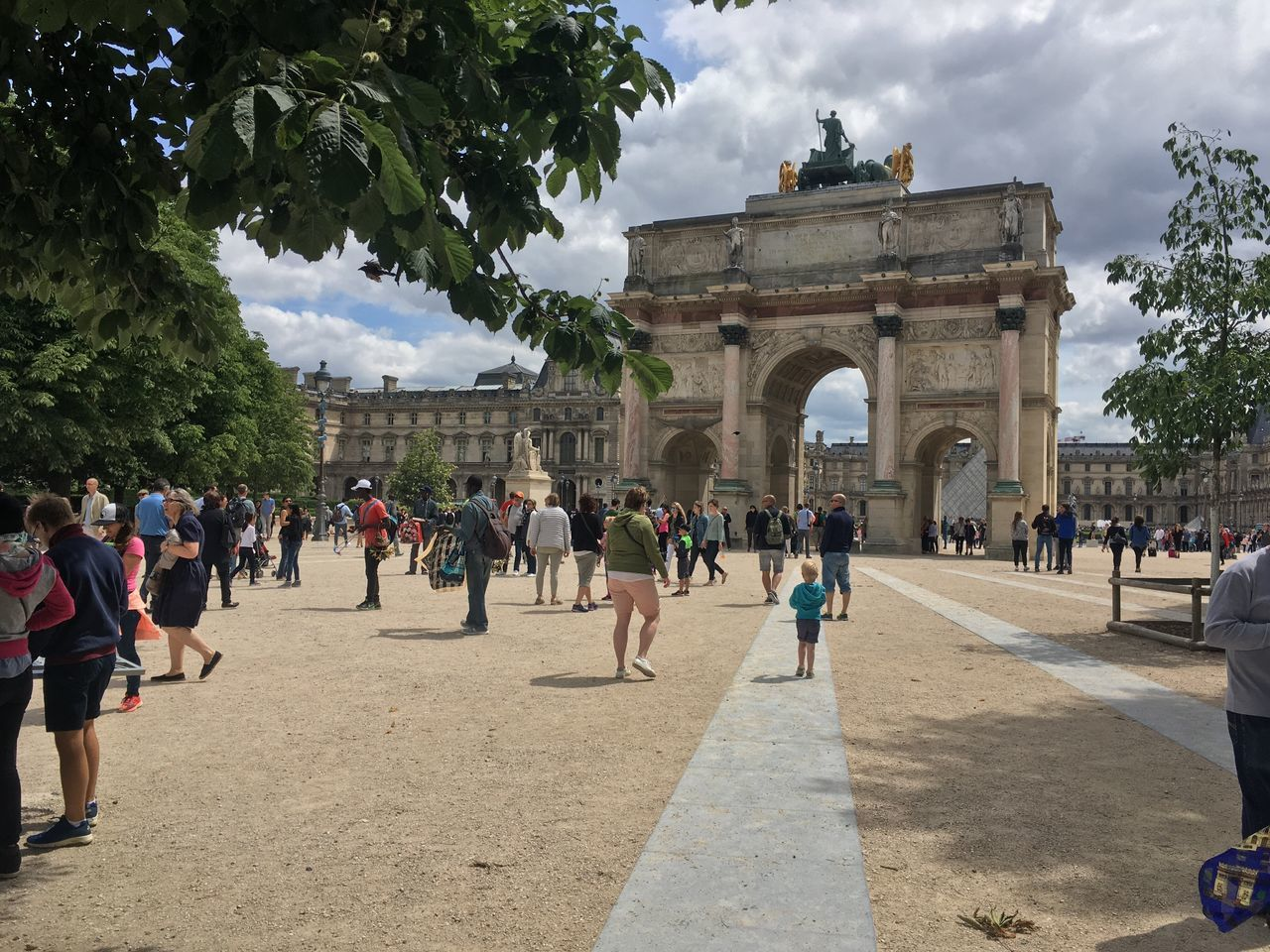 large group of people, travel destinations, tourism, cloud - sky, triumphal arch, history, sky, travel, real people, architecture, built structure, monument, arch, mixed age range, day, leisure activity, outdoors, vacations, women, men, tree, building exterior, people
