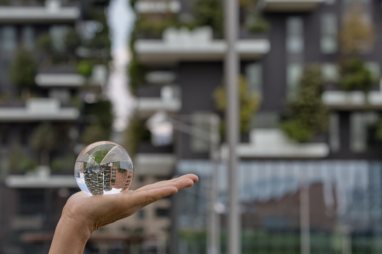 Bosco Verticale (Vertical Forest), designed by Stefano Boeri Adult Architectural Detail Architectural Feature Architecture Architecture_collection Architecturelovers Close-up Crystal Ball Crystal Ball Photography Day Facade Building Facade Detail Facades Façade Focus On Foreground Holding Human Body Part Human Hand One Person One Woman Only Only Women Outdoors Reflection Reflections