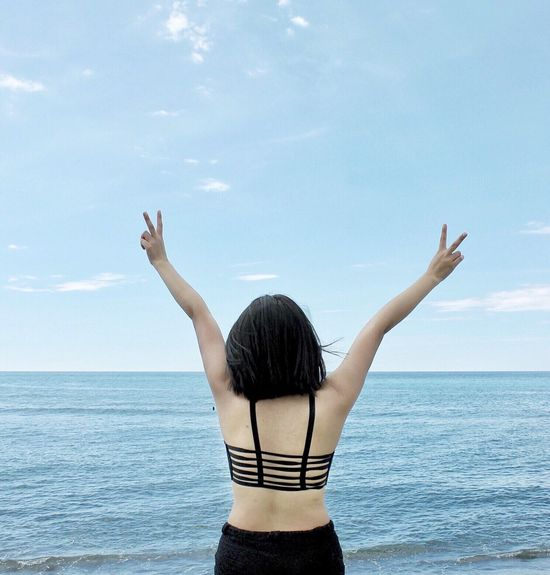 Vacations Beach Sea Rear View Horizon Over Water Arms Raised Standing Lifestyles Leisure Activity Water Waist Up Person Arms Outstretched Freedom Sky Enjoyment Carefree Scenics