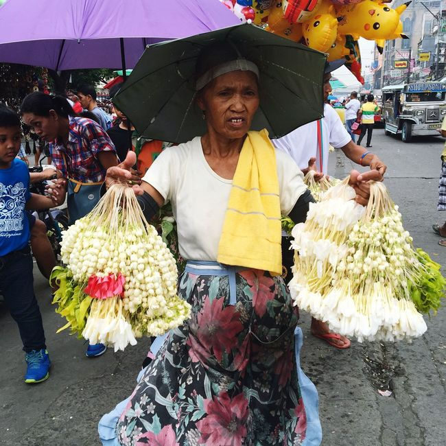 A woman sells sampaguita jasmine flower lei outside a church in Baclaran, Paranaque City, Metro Manila. Lifestyles Front View Standing Freshness Flower Retail  Flower Vendor Lei Jasmine Flower Philippines Metro Manila People And Places