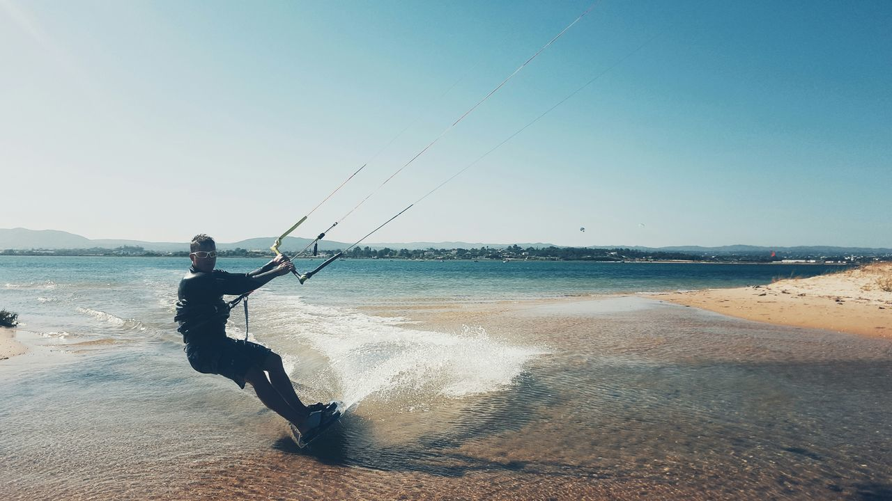 sea, water, horizon over water, beach, nature, one person, shore, real people, full length, day, beauty in nature, outdoors, scenics, leisure activity, men, clear sky, sand, motion, standing, sky, vacations, wave, one man only, people