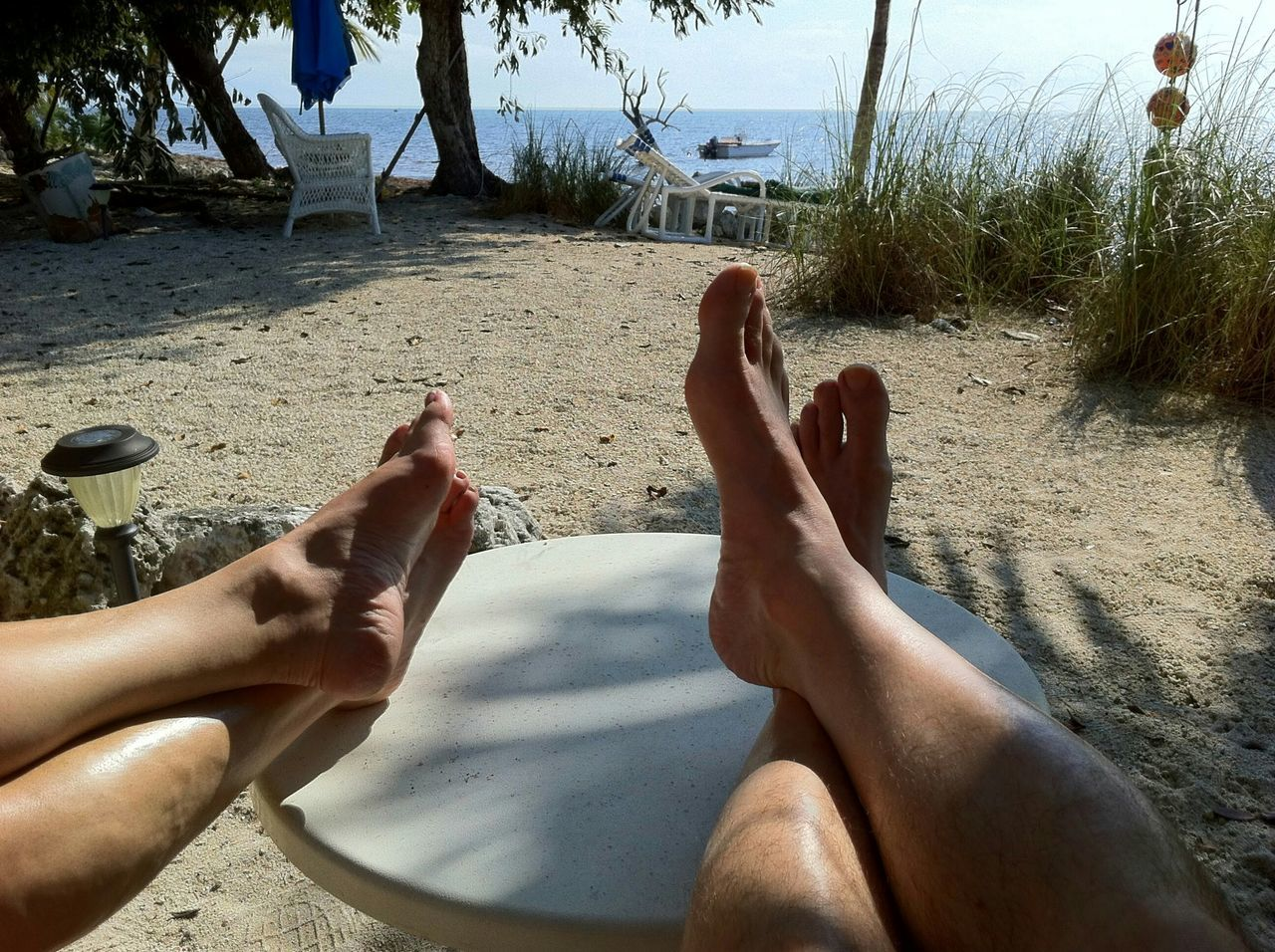 barefoot, human leg, low section, human foot, human body part, real people, beach, personal perspective, sand, leisure activity, day, sunlight, outdoors, togetherness, vacations, two people, relaxation, shadow, men, lifestyles, women, tree, close-up, nature, adult, people