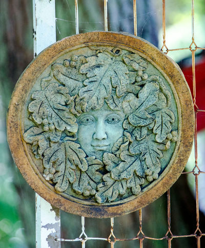 a face peers out of a circle of fall leaves in this creative artistic sculpture. god of autumn? Autumn Leaves Nature Art And Craft Close-up Day Face Human Representation Leaves No People Outdoors Place Of Worship Sculpture Spirituality Statue