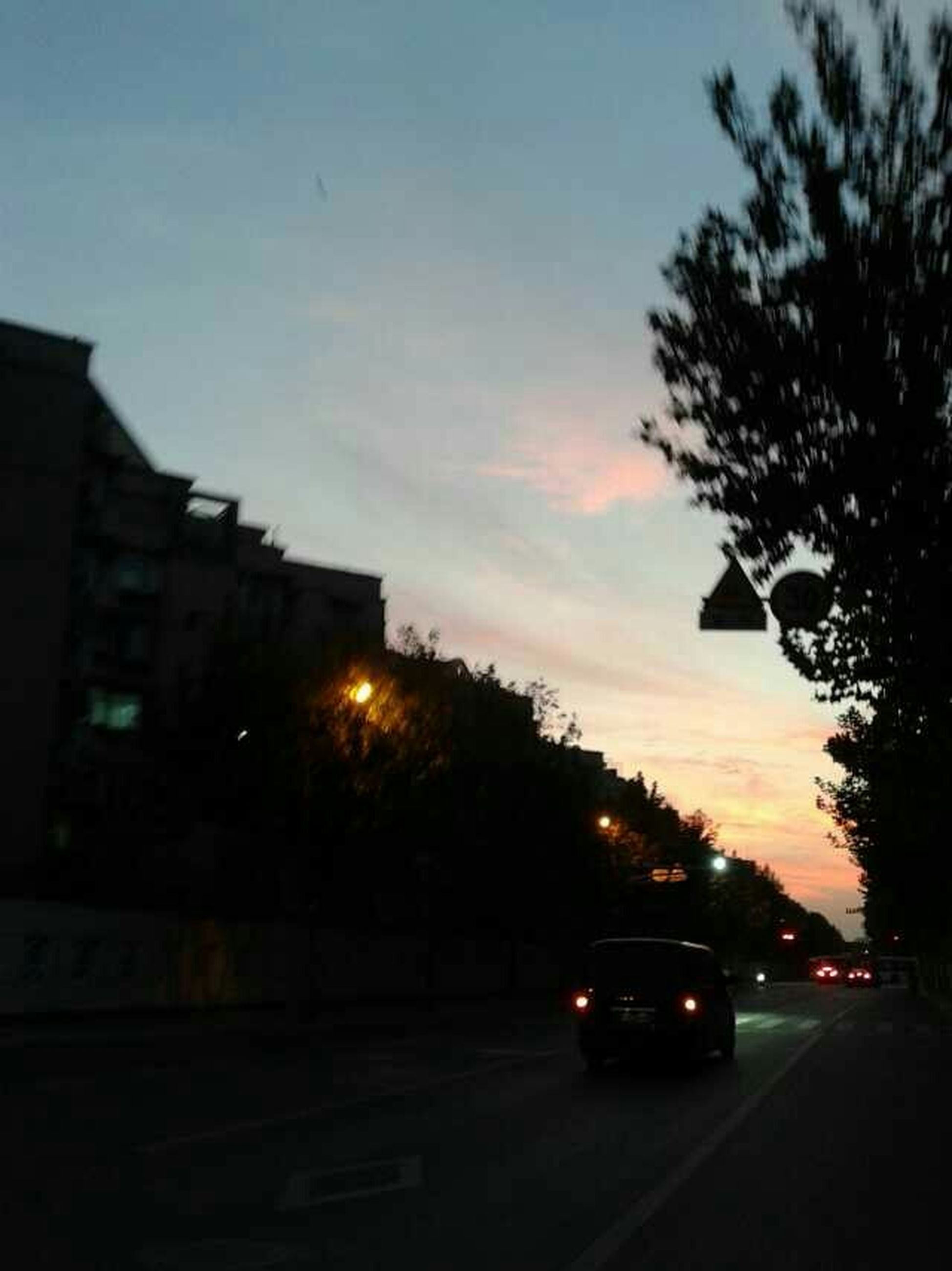 car, sunset, transportation, land vehicle, street, road, tree, silhouette, sky, building exterior, mode of transport, city, built structure, architecture, dusk, traffic, street light, illuminated, outdoors, no people