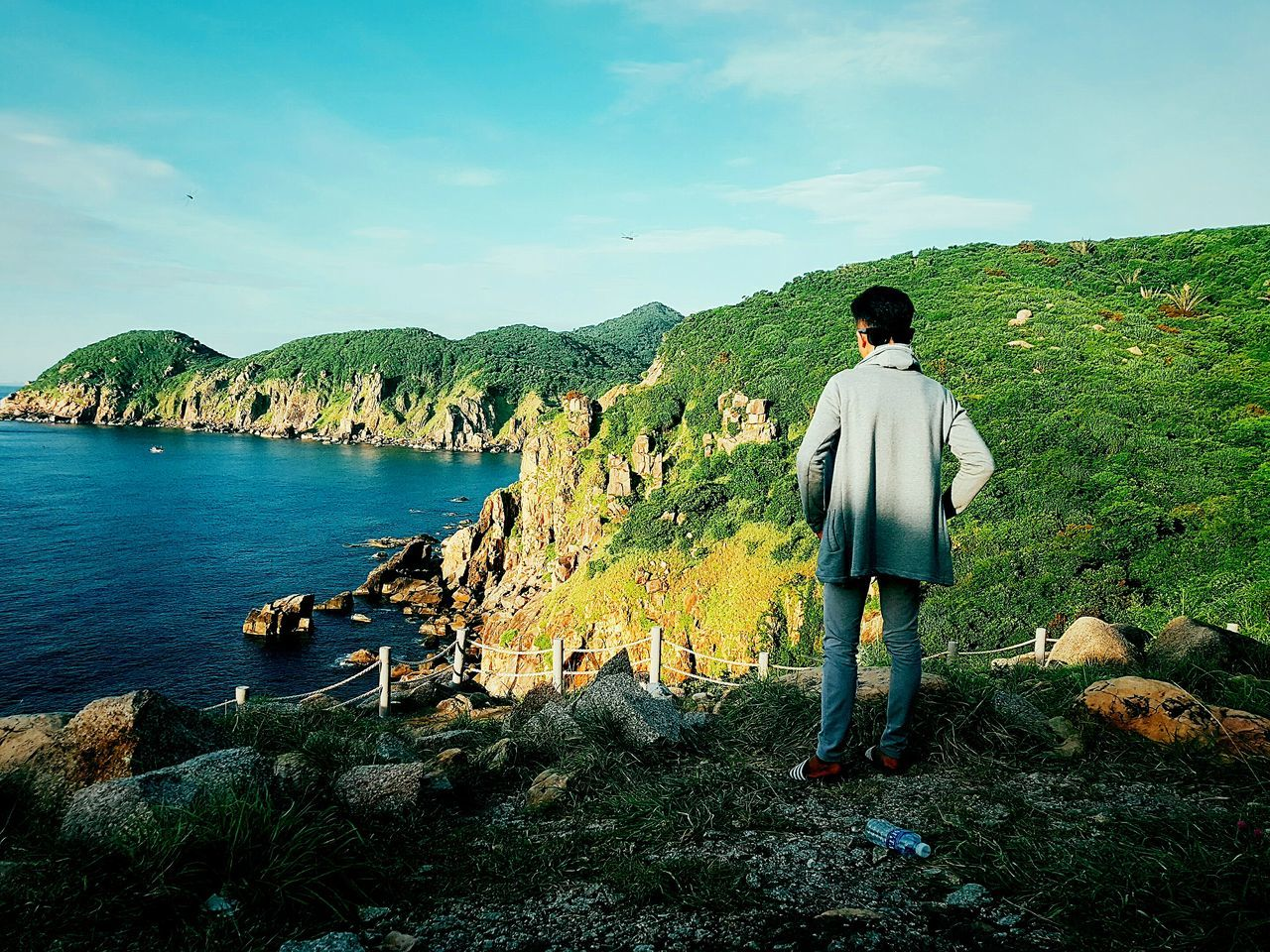 real people, one person, full length, rear view, nature, day, casual clothing, men, lifestyles, standing, leisure activity, rock - object, scenics, beauty in nature, sky, outdoors, tranquil scene, tree, mountain, water, young adult, one man only, people