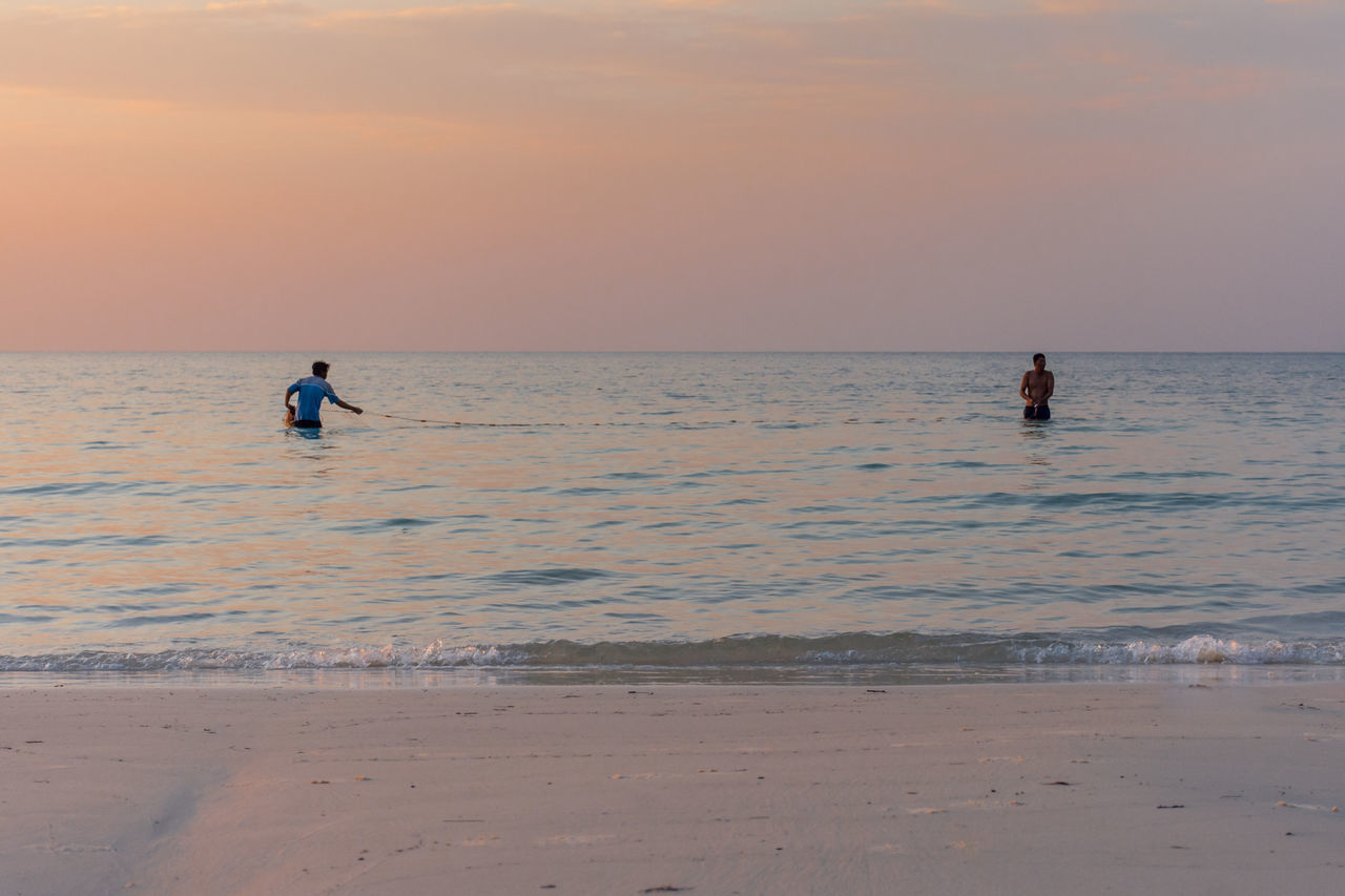 2 fishermen catch fish with a net off the beach at sunset. Beach Blue Calm Catch Clouds Clouds And Sky Day Fisherman Fishing Horizon Over Water Nature Ocean Orange Outdoor Pursuit Outdoors People Sea Still Sunset Tranquil Scene Tranquility Water White Sand